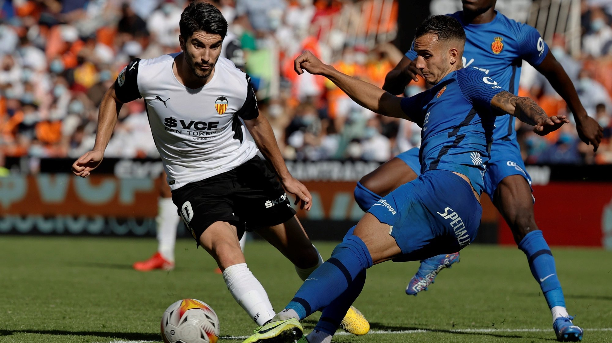 epa09541389 Valencia's Carlos Soler (L) fights for the ball with Franco Matias Russo of Mallorca during the Spanish LaLiga soccer match between Valencia CF and RCD Mallorca  played at Mestalla stadium in Valencia, eastern Spain, 23 October 2021.  EPA/KAI FOERSTERLING