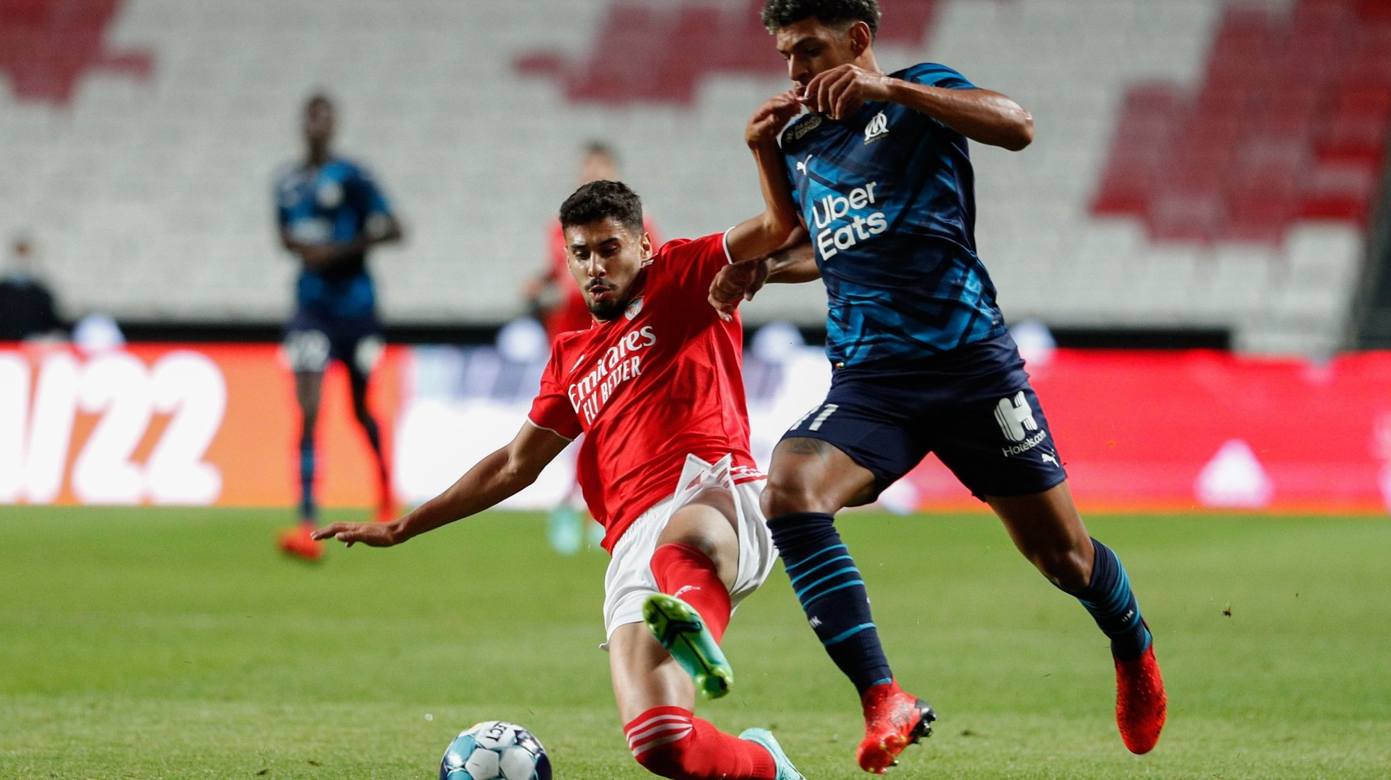 epa09365540 Benfica's player Gil Dias (L) in action against Olympique Marseille's player Luis Henrique (R), during the pre-season friendly test soccer match between Benfica and Olympique Marseille at Luz Stadium in Lisbon, Portugal, 25 July 2021.  EPA/ANTONIO COTRIM