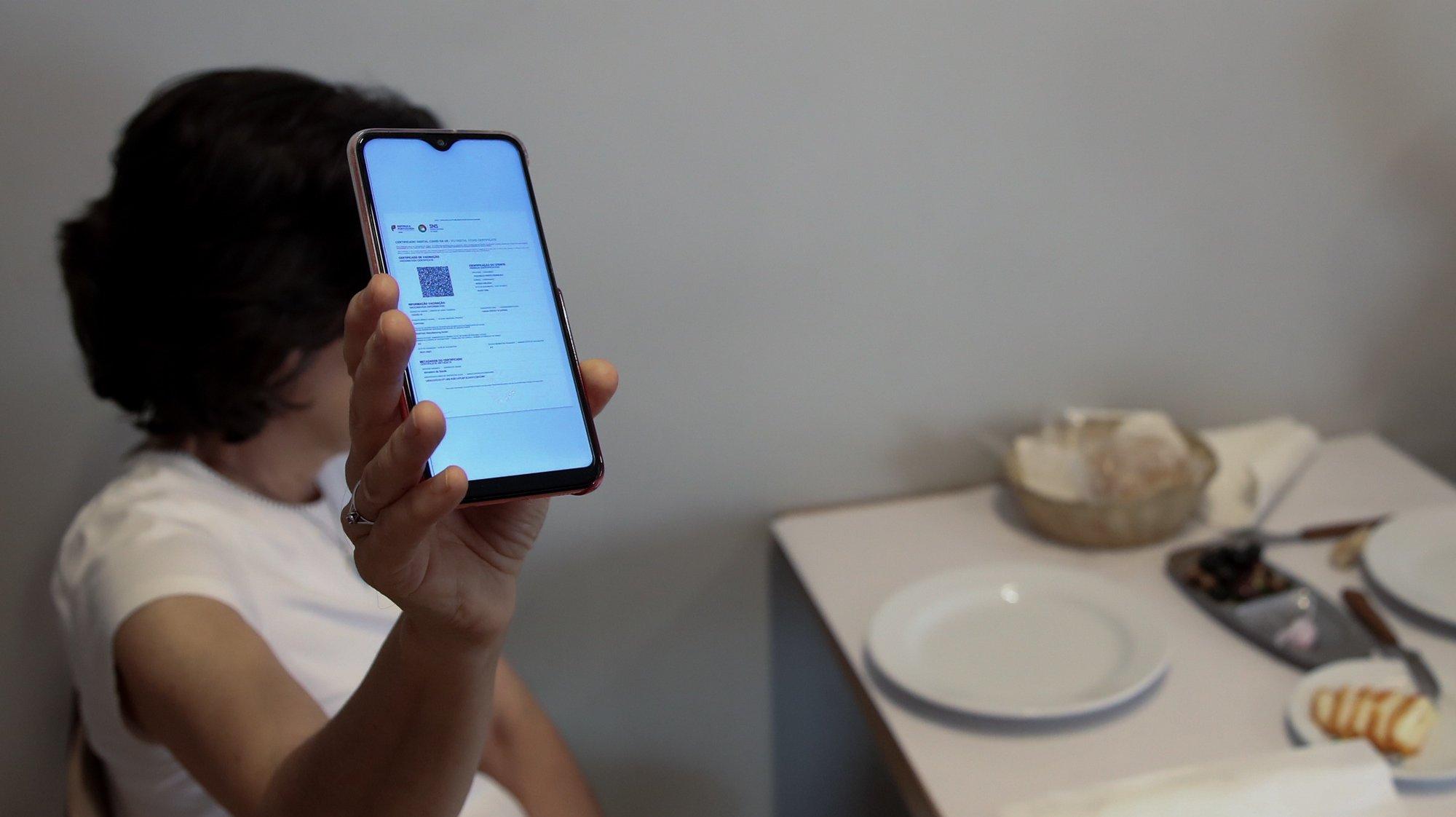 Cliente exibe o certificado digital no interior de um restaurante em Lisboa, após o Governo decreta que os restaurantes em concelhos de risco elevado ou muito elevado – um total de 60 – passam a ter de exigir certificado digital ou teste negativo à covid-19 a partir das 19:00 de sexta-feira e aos fins de semana para refeições no interior, Lisboa, 10 de julho de 2021. As pessoas em esplanadas que precisarem de entrar nos restaurantes para acesso aos serviços comuns, como instalações sanitárias, ou para efetuarem pagamento, estão dispensadas de apresentar um teste negativo à covid-19 ou o certificado digital. MANUEL DE ALMEIDA/LUSA