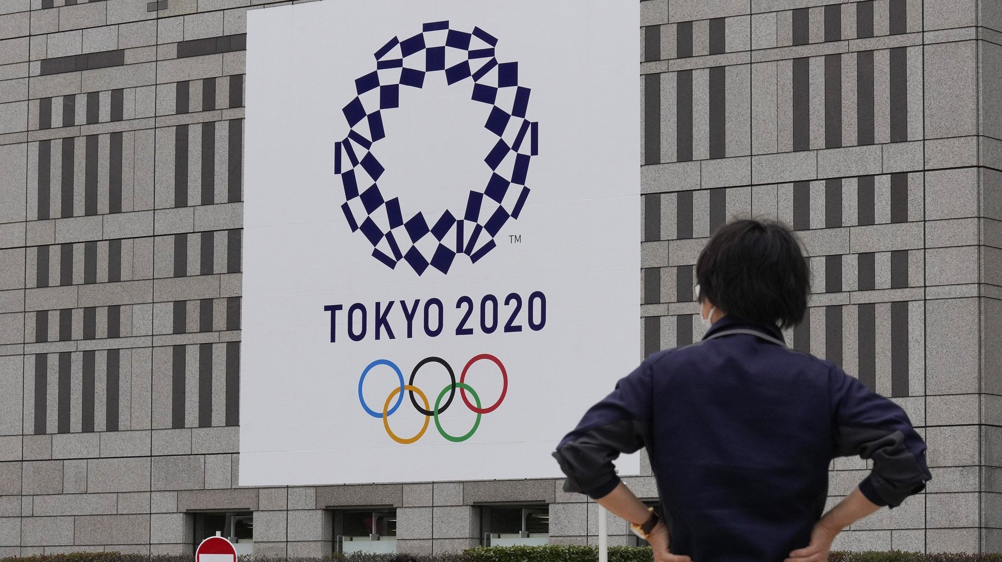 epa09293039 Pedestrians walk past the logo of the Tokyo 2020 Olympic Games decorated on the wall of Tokyo Metropolitan Government office building, Japan, 22 June 2021. Tokyo and Japan will mark one month before the opening of the Tokyo 2020 Olympic Games on 23 June 2021. The Summer Games was rescheduled from 2020 due to COVID-19 Coronavirus pandemic.  EPA/KIMIMASA MAYAMA