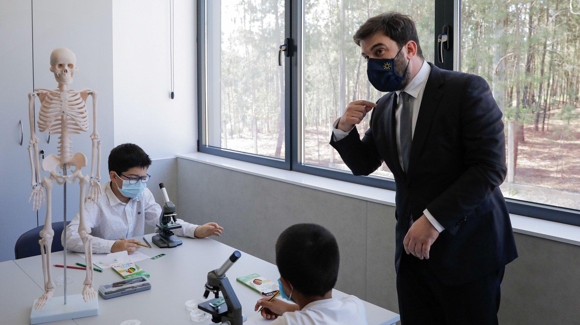 O ministro da Educação, Tiago Brandão Rodrigues (D), conversa com alunos durante a visita e inauguração do Centro Escolar de Carvoeira, Caxarias, Ourém, 05 de abril de 2021. PAULO CUNHA /LUSA