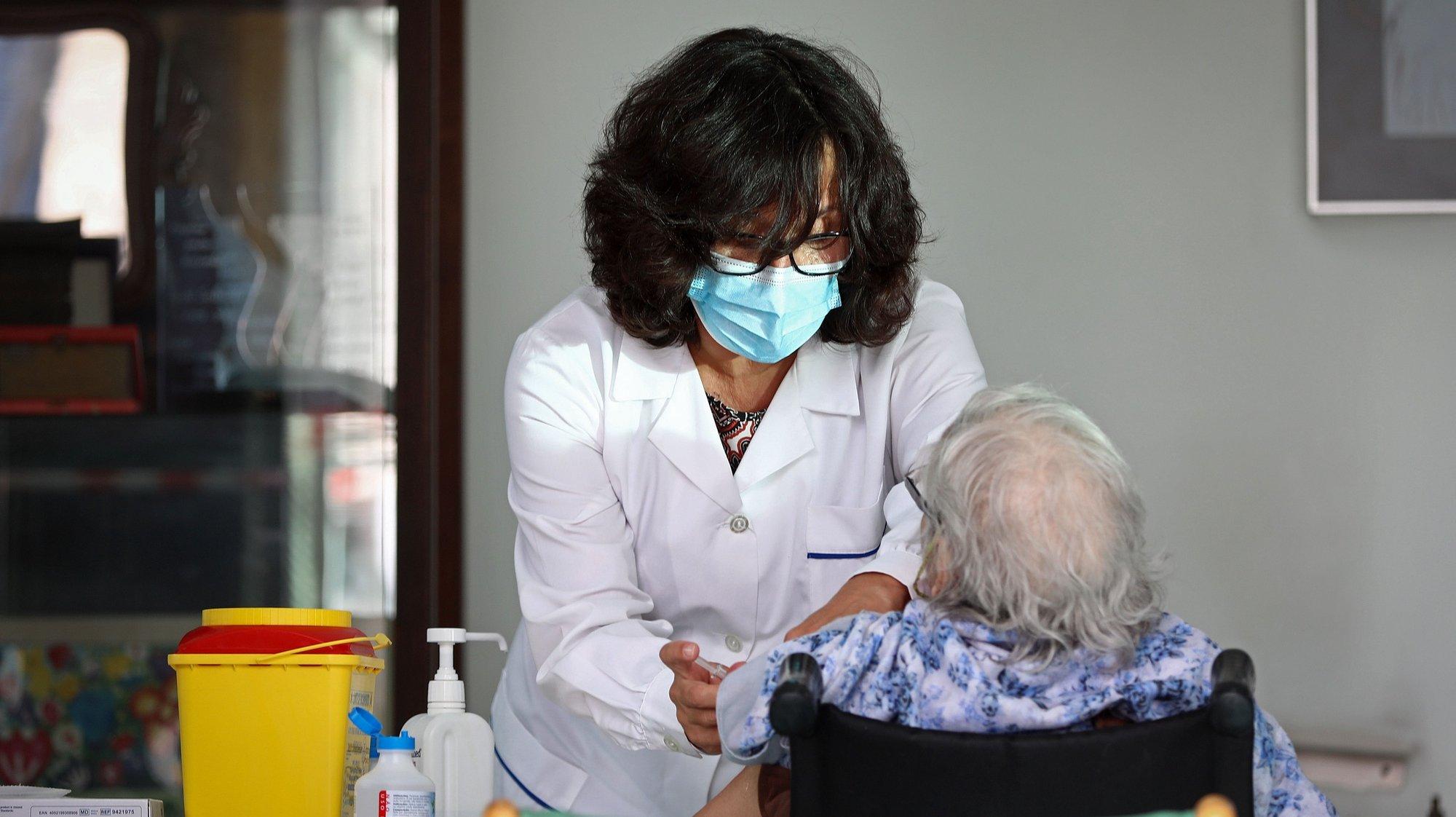 """Uma utente do Lar da Casa do Artista é vacinada contra a gripe, durante uma visita da ministra da Saúde, Marta temido (ausente na foto), em que enfermeiros do Agrupamento de Centros de Saúde (ACES) Lisboa Norte vão vacinar idosos e profissionais, para assinalar o início da época vacinal contra a gripe sazonal 2020, em Lisboa, 28 de setembro de 2020. Hoje tem início a 1ª fase de vacinação gratuita contra a gripe sazonal, a qual  inclui """"residentes, utentes e profissionais de estabelecimentos de respostas sociais, doentes e profissionais da rede de cuidados continuados integrados, profissionais do SNS e grávidas"""". ANTÓNIO PEDRO SANTOS/LUSA"""