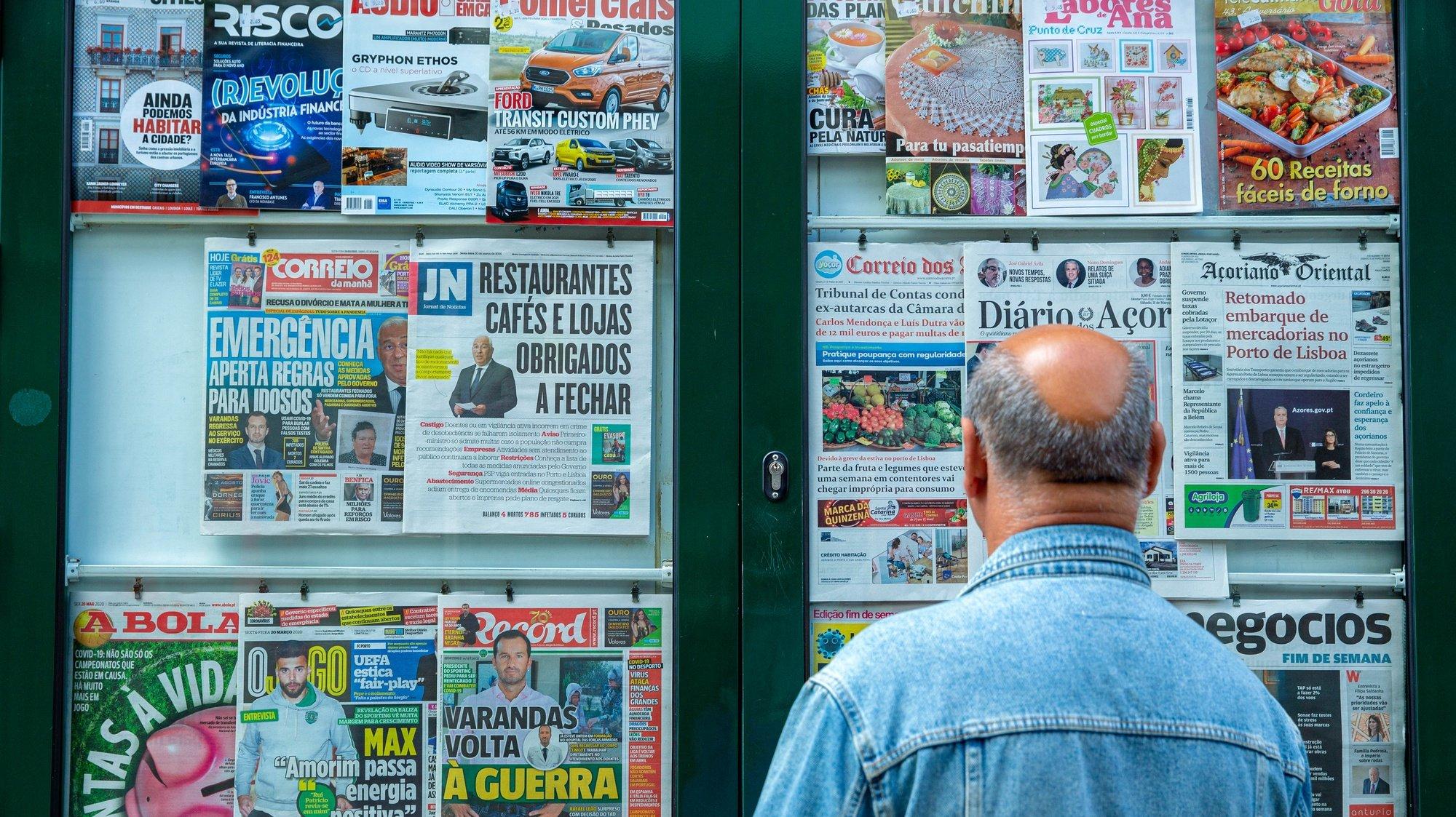 Um homem lê as capas dos jornais exposta na vitrina de um quiosque de rua em Ponta Delgada, ilha de São Miguel, Açores, 21 de março de 2020. Em Portugal, há 12 mortes e 1.280 infeções confirmadas. Portugal encontra-se em estado de emergência desde as 00:00 de quinta-feira e até às 23:59 de 02 de abril. EDUARDO COSTA/LUSA