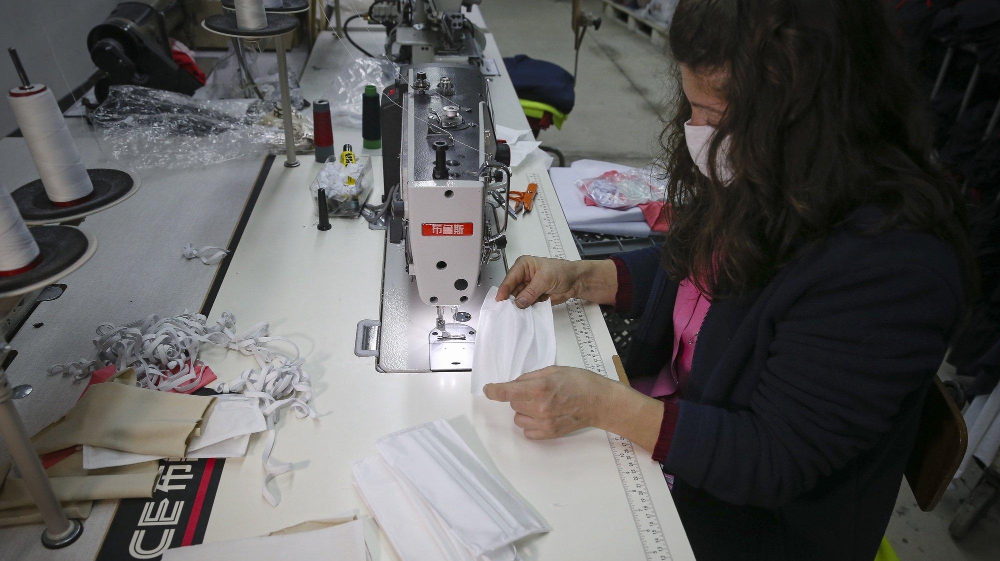 Funcionárias de uma empresa têxtil produzem máscaras descartáveis, em Barcelos, 21 de abril de 2020. Nesta altura, a Têxtilobo - The Textile Company, instalada na freguesia de Carapeços, está já certificada, pelo Centro Tecnológico das Indústrias Têxtil e do Vestuário de Portugal (CITEVE), para a produção de máscaras descartáveis. (ACOMPANHA TEXTO). JOSÉ COELHO/LUSA