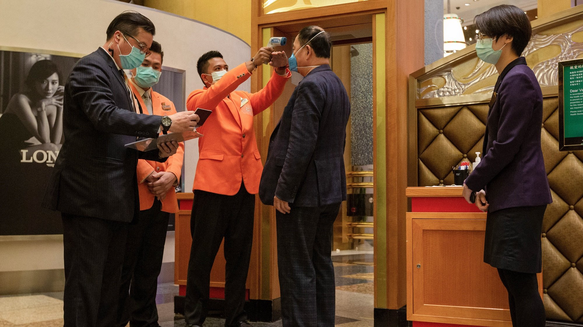epa08228736 Casino workers workers wearing protective masks check the temperature of a visitor to detect traces of Coronavirus infection, at a Casino in Macao, China, 20 February 2020. Twenty-nine casinos are to reopen starting 20 February, and 12 remain closed, the authorities of the gambling capital said, one of the regions that have identified cases of infection by the coronavirus Covid-19.  After 15 days of closure, Macau's government said on 17 February that the casinos could reopen, giving operators 30 days to return to business.  EPA/CARMO CORREIA