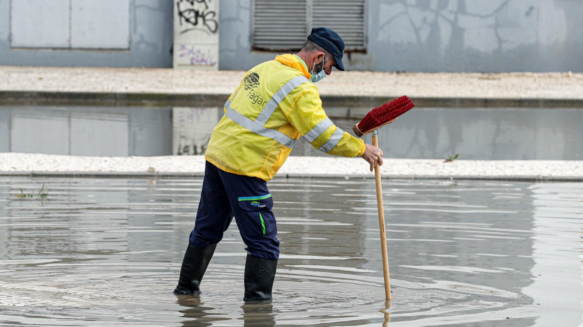 Um funcionário camarário ajuda na limpeza das ruas inundadas devido à chuva forte que caiu esta manhã no Algarve, em Faro, 05 de fevereiro de 2021. LUÍS FORRA/LUSA