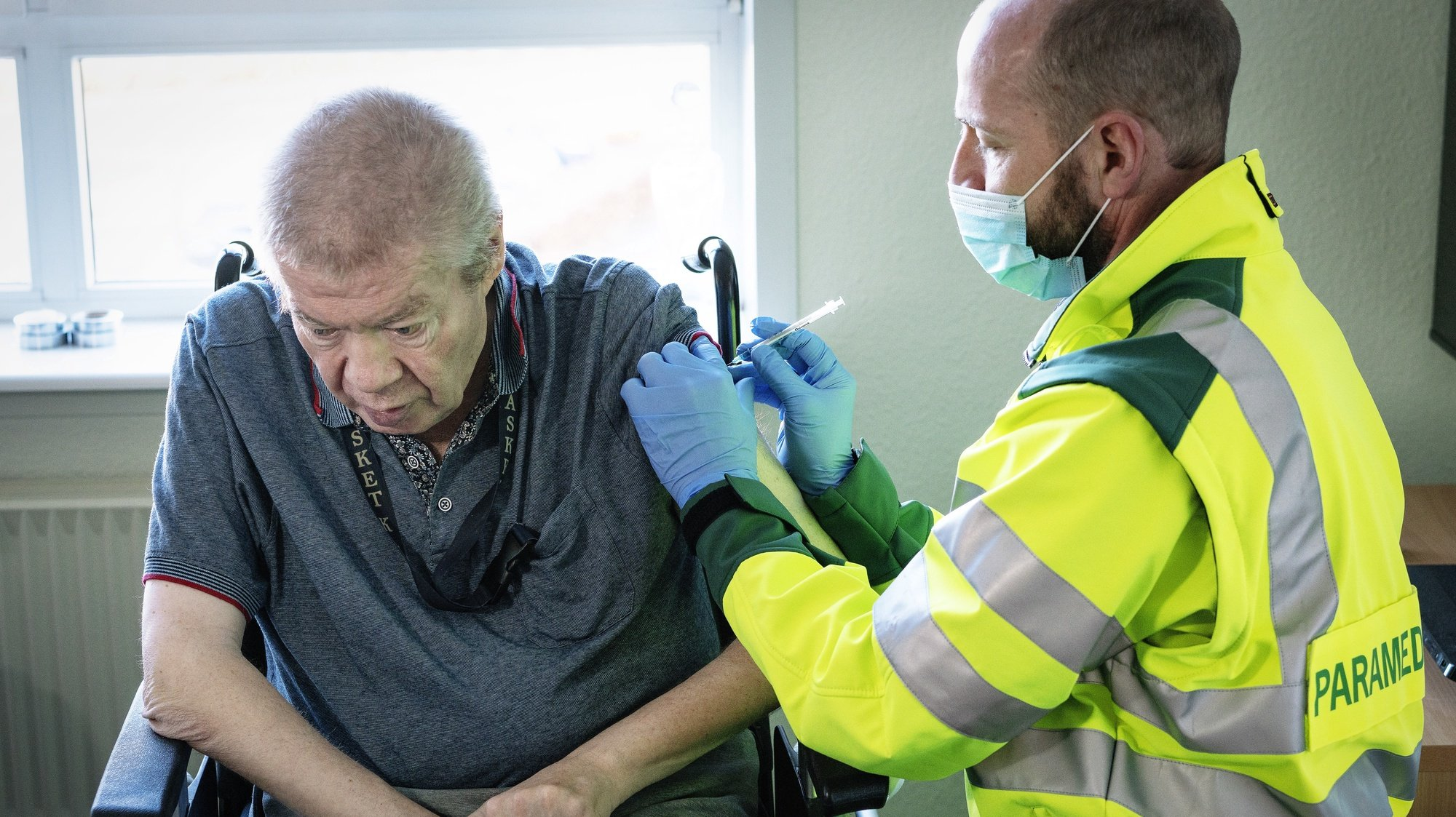 epa09053200 A 67-year-old Aage Steen Jensen, who is a kidney patient, is vaccinated in his own home in Aalborg, Denmark, 05 March 2021. Elderly, over 65, who cannot be transported to a coronavirus vaccination site, receive both practical help and personal care. On 05 March, the first seven persons from Northern Jutland will receive the first vaccinations against Covid-19 in their own homes. Paramedics from the North Jutland Region will perform the vaccinations.  EPA/BO AMSTRUP  DENMARK OUT