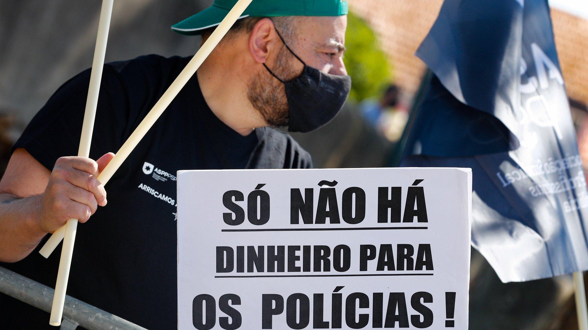 """Um participante exibe um cartaz onde se lê """"Só Não Há Dinheiro Para Os Polícias!"""" durante a jornada de protesto dos elementos da PSP e da GNR com o objetivo de """"sensibilizar todos os cidadãos para a problemática da não atribuição do suplemento de risco aos polícias da PSP e militares da GNR"""", junto ao Palácio da Ajuda, local onde decorre a reunião do Conselho de Ministros, em Lisboa, 15 de julho de 2021. Convocado pelos sindicatos da Polícia de Segurança Pública (PSP) e associações da Guarda Nacional Republicana (GNR) - Associação Nacional de Guardas; Associação Nacional de Sargentos da Guarda Associação Sócio Profissional Independente dos Profissionais da GNR; Associação Sindical Autónoma de Polícias; Organização Sindical dos Polícias; Sindicato Independente de Agentes de Polícia; Sindicato Independente Livre Polícia; Sindicato Nacional da Polícia; Sindicato Nacional Carreira de Chefes PSP; Sindicato Nacional Oficiais de Polícia; Sindicato Profissionais de Polícia; Sindicato de Polícia pela Ordem e Liberdade; Sindicato Vertical da Carreira de Polícia. ANTÓNIO COTRIM/LUSA"""