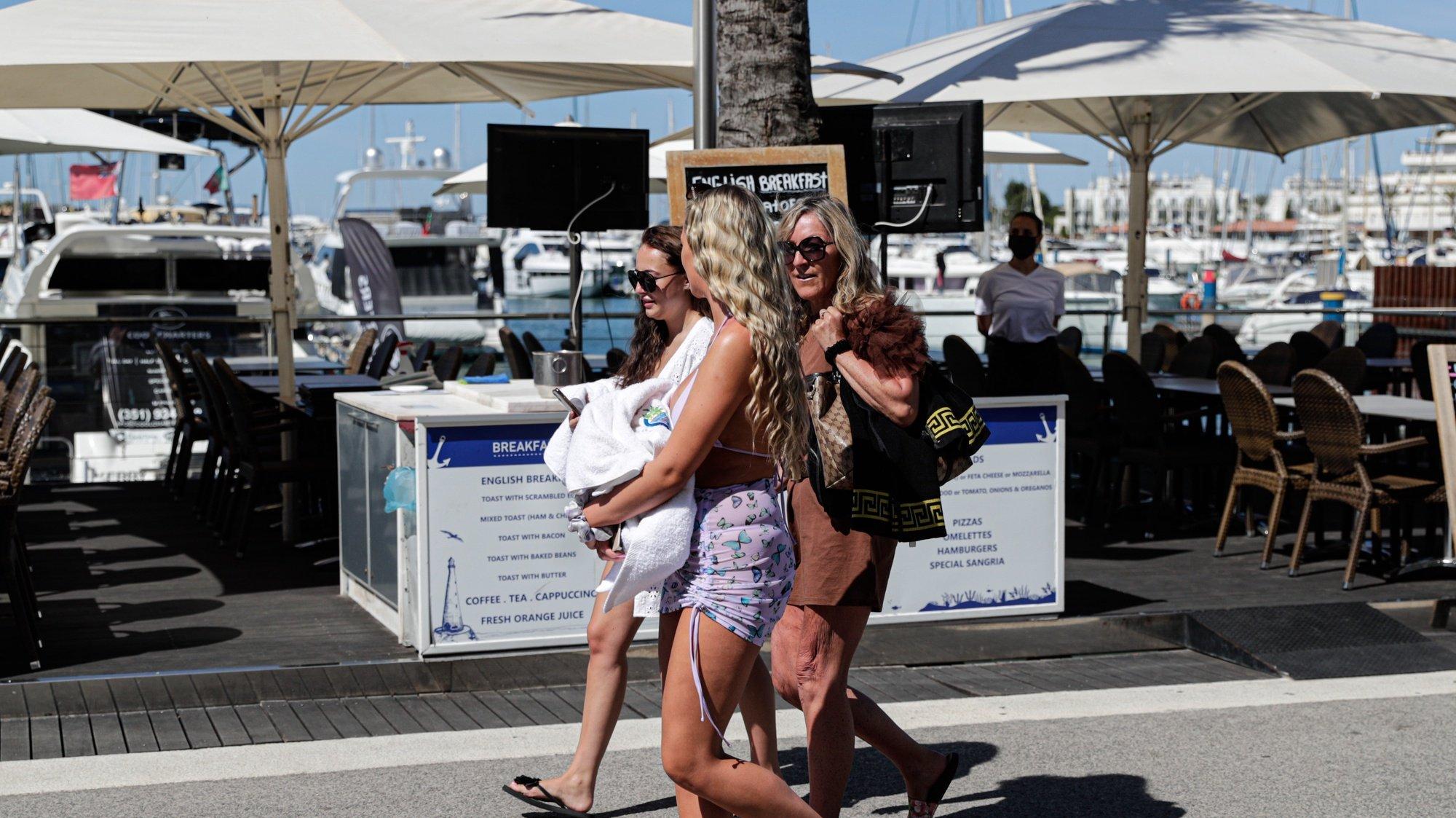 Turistas passeiam na marina de Vilamoura, 19 de maio de 2021. Dando início aos planos de retomada do turismo, Portugal passou a permitir na segunda - feira, 17 de maio, viagens não essenciais do Reino Unido e de países da União Europeia, o que fez com que muitos turistas se deslocassem de férias para o Algarve.  (ACOMPANHA TEXTO) LUÍS FORRA/LUSA