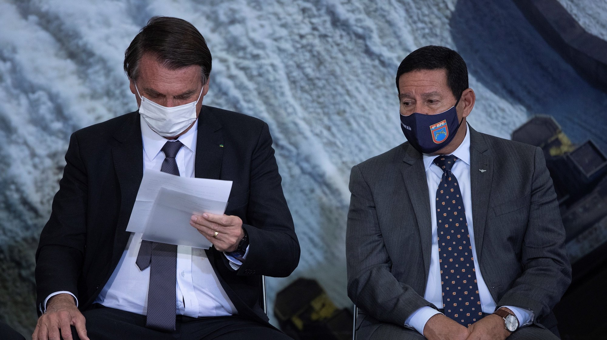 epa09343160 The President of Brazil, Jair Bolsonaro, and the Vice President Hamilton Mourao (R) take part in the sanction ceremony of the Eletrobras Capitalization Law, at the Planalto Palace in Brasilia, Brazil, 13 July 2021. Bolsonaro sanctioned with some vetoes the Provisional Measure that regulates the privatization process of the state giant Eletrobras, the largest electricity company in Latin America, according to the Official Gazette of the Union published on 13 July.  EPA/Joedson Alves