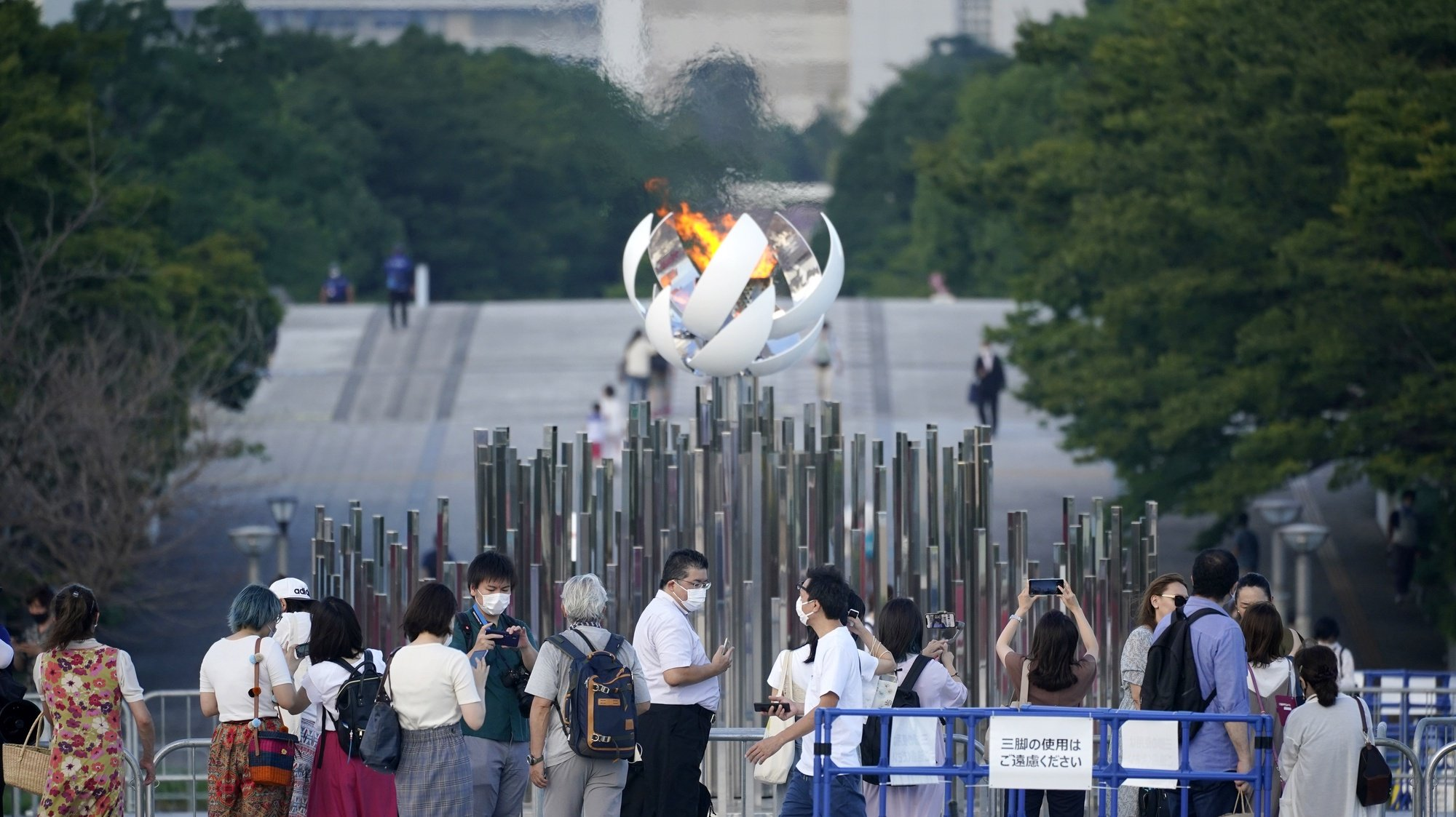 epa09373419 People take photos of the Olympic Flame in Tokyo, Japan, 28 July 2021. The Japanese capital recorded 3,177 new coronavirus cases on 28 July, hitting a new daily record for the second day in a row. It reported 2,848 cases on 27 July, adding further pressure on the country's health care system.  EPA/FRANCK ROBICHON