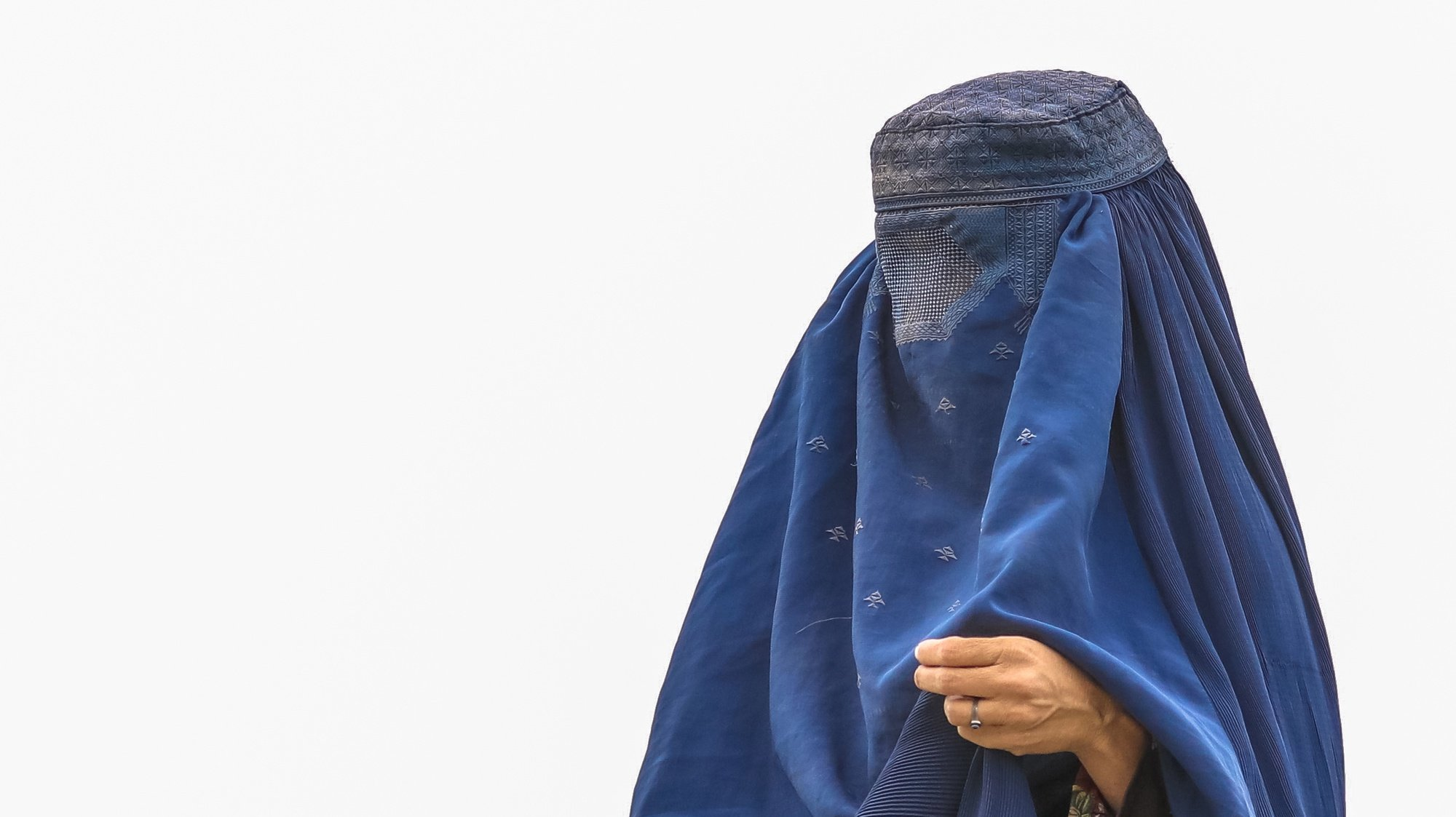 epa09414570 An Afghan burqa-clad women from northern provinces stands near her shelter after she fled from her home due to the fighting between Taliban and Afghan security forces, in a public park in Kabul, Afghanistan, 14 August (issued 15 August). The Taliban captured Mazar-i-Sharif, the country's fourth-largest city and the government's last major stronghold in the north on 14 August, as they tightened their grip on the country and closed in on Kabul. Most of the remote districts of the provinces have already fallen to the Taliban in the past three months.  EPA/HEDAYATULLAH AMID