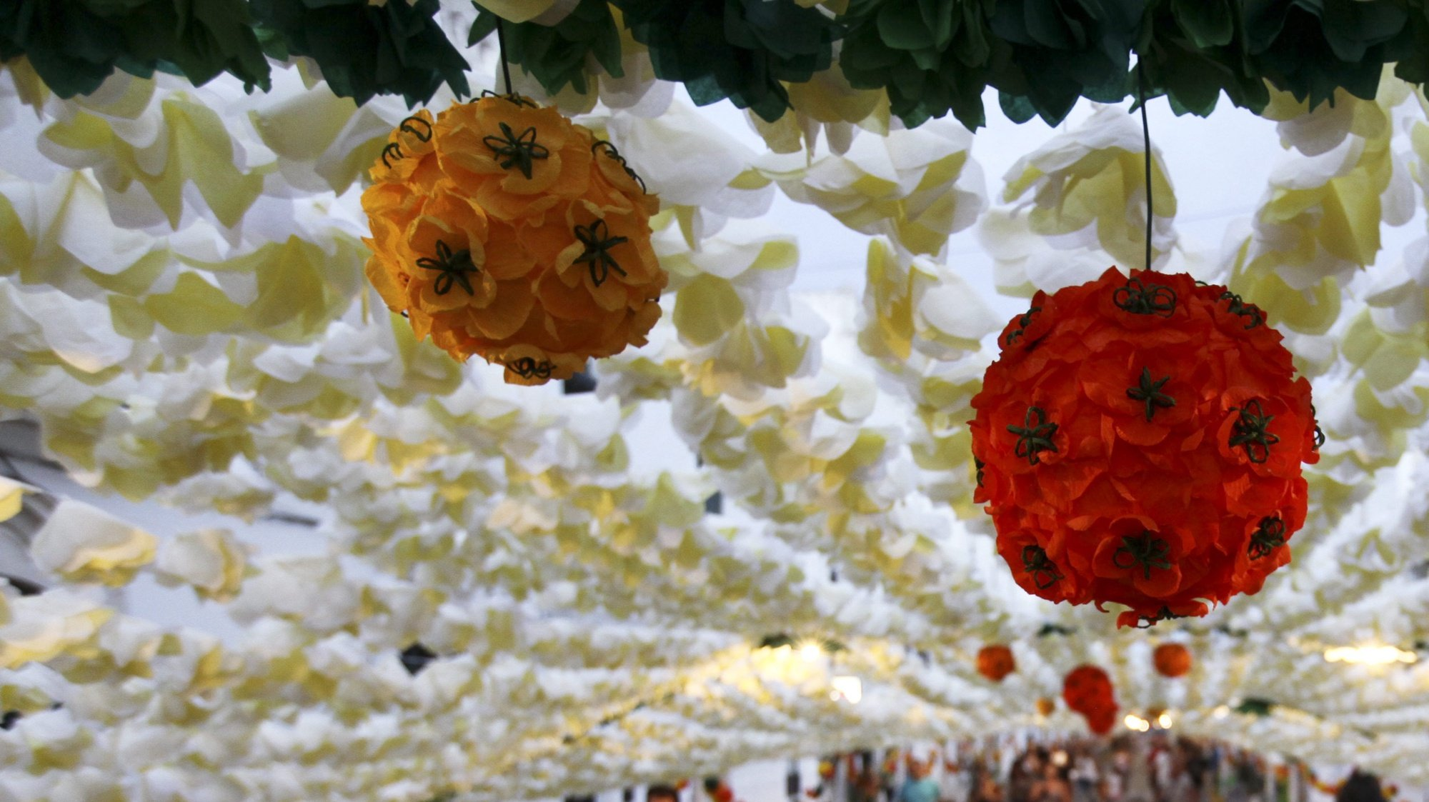 epa04895426 Visitors walk by the street covered with paper flowers during the Festas do Povo (People Fest) in Campo Maior, 180 Km from Lisbon, Portugal, 23 August 2015. The festival consist of the decoration of the streets of Campo Maior, especially the Old Town, with paper flowers and other objects in card and paper, made by the population. The latest Festas do Povo took place in 2011 and brought to the Alentejo town about one million people, and have been used nearly 30 tons materials and 7,500 volunteer people.  EPA/NUNO VEIGA