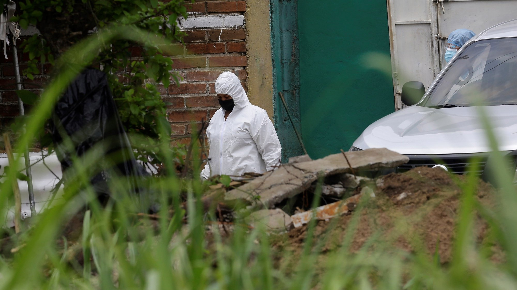 epa09217666 Forensic teams, members of the Attorney General's Office, and police officers work during a search for human remains at the house of former police officer Hugo Ernesto Osorio, who is being investigated for homicide, in Chalchuapa, northwest of San Salvador, El Salvador, 20 May 2021 (issued 21 May 2021).  EPA/RODRIGO SURA