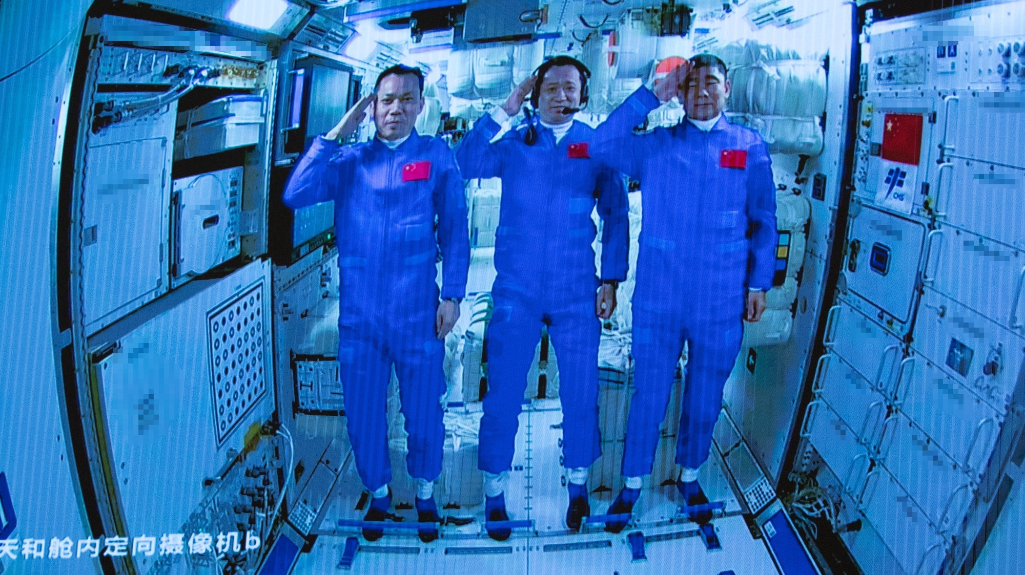 epa09281811 A screen image made available by Xinhua News Agency captured at the Beijing Aerospace Control Center shows three Chinese astronauts onboard the Shenzhou-12 spaceship saluting after entering the Tianhe space station core module in Beijing, China, 17 June 2021 (issued 18 June 2021). China launched the Shenzhou-12 spacecraft carrying three crew members Tang Hongbo, Nie Haisheng, and Liu Boming to the orbiting Tianhe core module for a three-month mission on 17 June. The mission is China's first manned spaceflight in almost five years.  EPA/XINHUA/JIN LIWANG MANDATORY CREDIT EDITORIAL USE ONLY/NO SALES