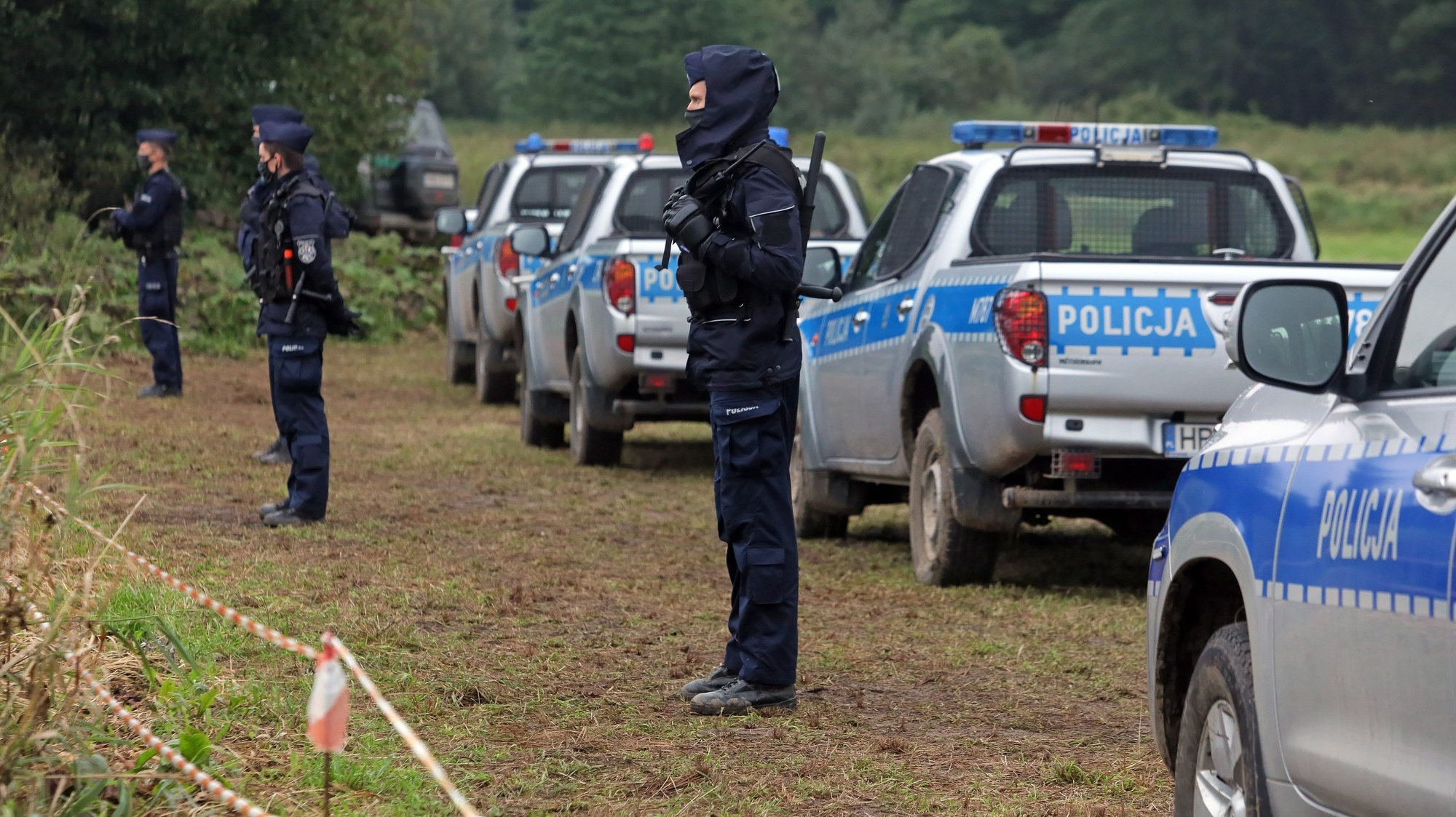 epa09436765 Polish police officers stand at the Polish-Belarusian border near Usnarz Gorny village, north-west Poland, 30 August 2021. The number of migrants from Iraq, Syria, Afghanistan and other countries trying to cross the Belarusian border into neighbouring EU states has increased sharply in recent months. According to official sources, a group of 24 people, including 20 men and four women but no children, camped at Usnarz Gorny on the Belarusian side of the Polish-Belarusian border.  EPA/ARTUR RESZKO POLAND OUT