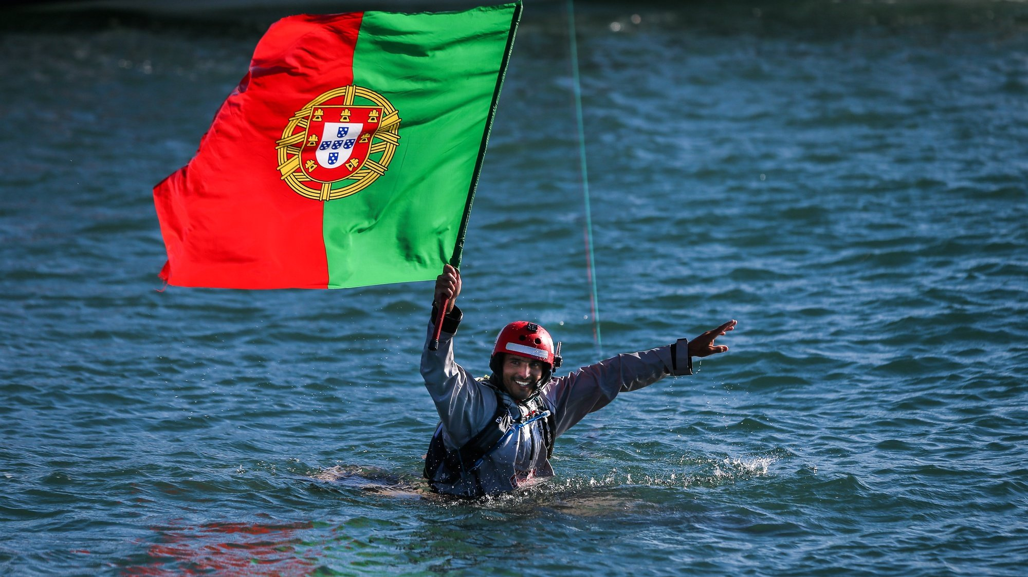 Portuguese kitesurfer, Francisco Lufinha, holds the Portugal flag as he arrives to Oeiras harbour after conquering a new kitesurf world record of the longest kitesurf trip with his partner the German Anke Brandt (not on the picture) between Azores Islands and continental Portugal, Oeiras, Portugal, 13 September 2017. MARIO CRUZ/LUSA