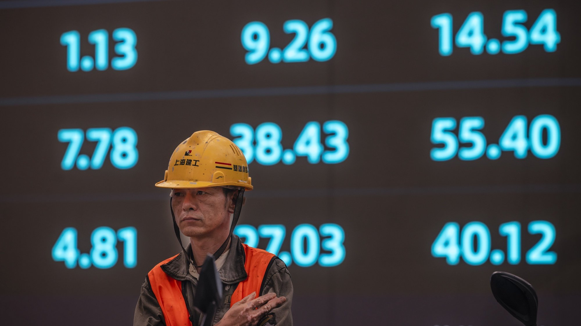 epa09510804 A worker stands in front of the screen showing newest stock exchange and economic data in Shanghai, China, 07 October 2021. A debt crisis and rising bond yields of China Evergrande Group made a whirlwind for other Chinese real estate developers who suspended their stock trading this week in the Hong Kong market. There are concerns and speculations in the Hong Kong stock market over the uncertainty and market value.  EPA/ALEX PLAVEVSKI