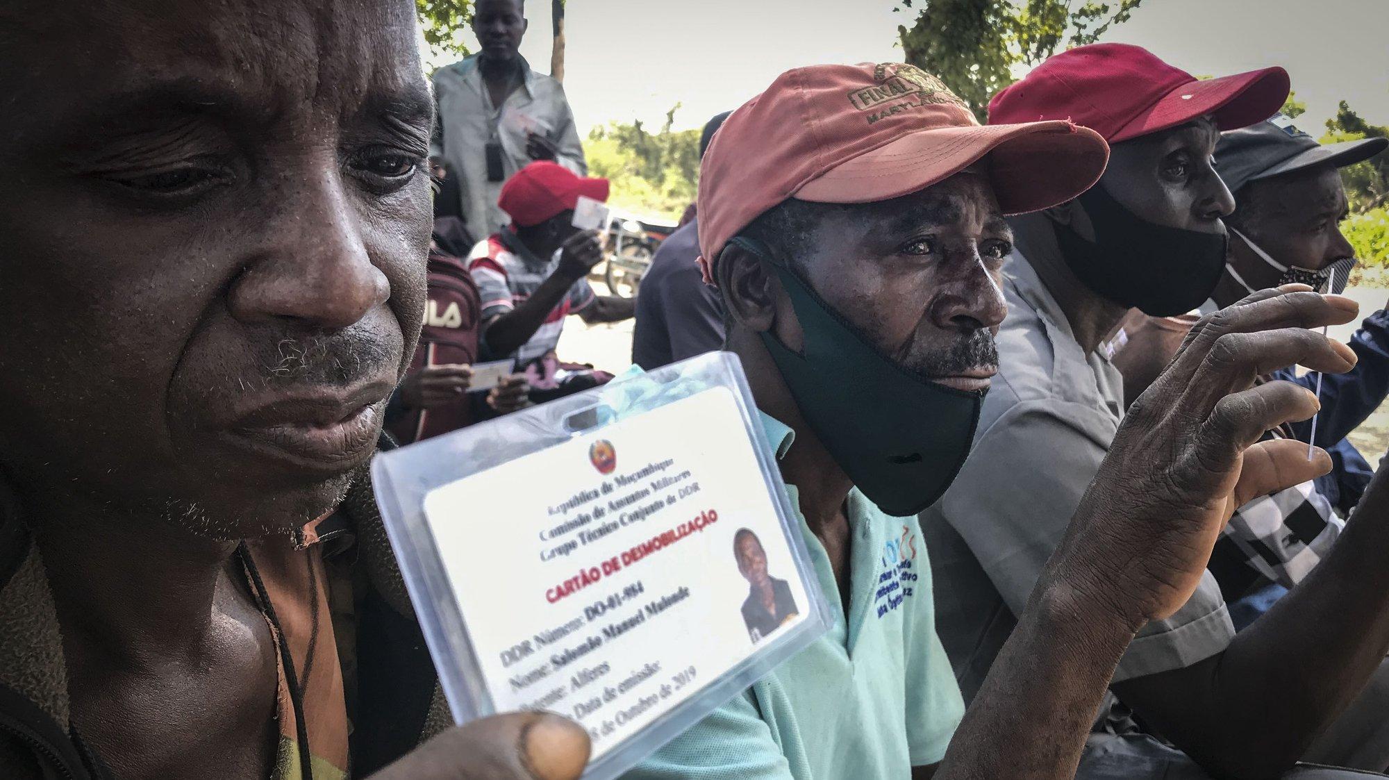 """Ex-guerrilheiros exibem o seu cartão de desmobilização, durante uma reunião de ex-guerrilheiros desmobilizados na aldeia de Nhamatanda, Moçambique, 24 de maio de 2021. O Presidente moçambicano tem feito um balanço positivo do processo de DDR, em diferentes discursos feitos nas últimas semanas e destacou os """"importantes avanços na implementação do processo, com 10 bases desativadas e 2.307 combatentes a entregar as armas, o equivalente a 44% do número total de guerrilheiros a desarmar"""". (ACOMPANHA TEXTO DA LUSA DO DIA 25 DE MAIO DE 2021). ANDRÉ CATUEIRA/LUSA"""