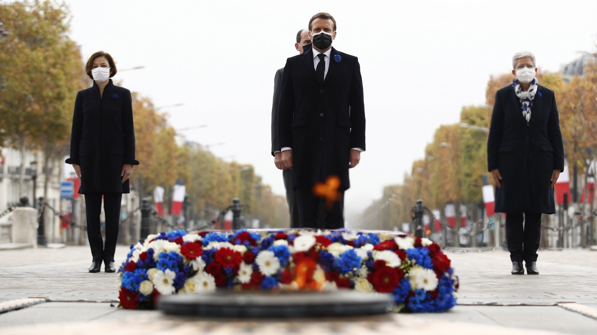 epa08812956 French President Emmanuel Macron (C) pays his repsects as French Prime Minister Jean Castex (rear C), French Junior Defence Minister Genevieve Darrieussecq (R) and French Defence Minister Florence Parly (L) stand behind during a ceremony at the Arc de Triomphe in Paris, France, 11 November 2020, as part of the commemorations marking the 102nd anniversary of the 11 November 1918 armistice, ending World War I (WWI).  EPA/YOAN VALAT / POOL