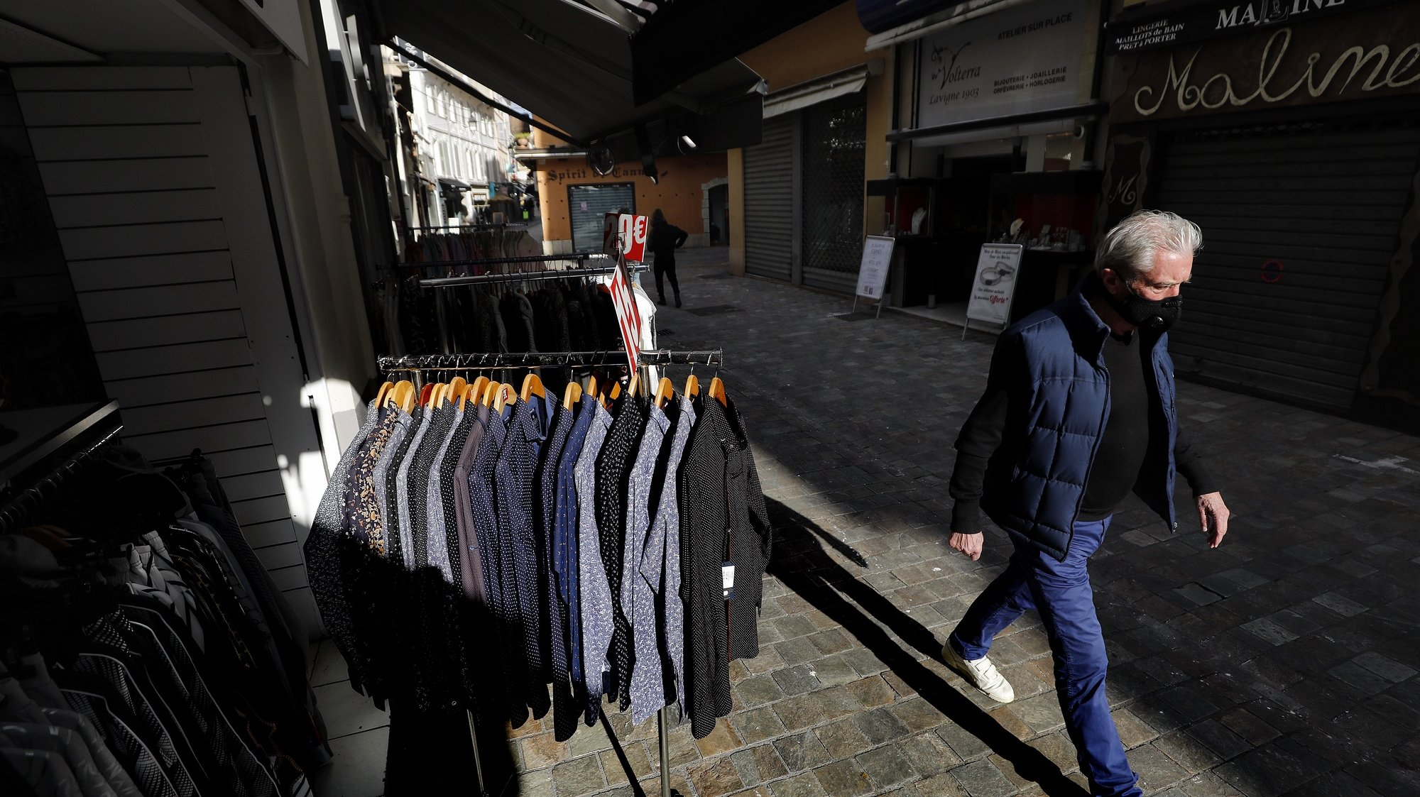 epa09097124 A man walks past a clothing store that displays these clothes on the streets during the lockdown in Cannes, France, 25 March 2021. New COVID-19 lockdown restrictions include the closure of 'non-essential' businesses, but the town halls of Cannes, Antibes, and Menton allow the sale of non-essential outdoor businesses.  EPA/SEBASTIEN NOGIER
