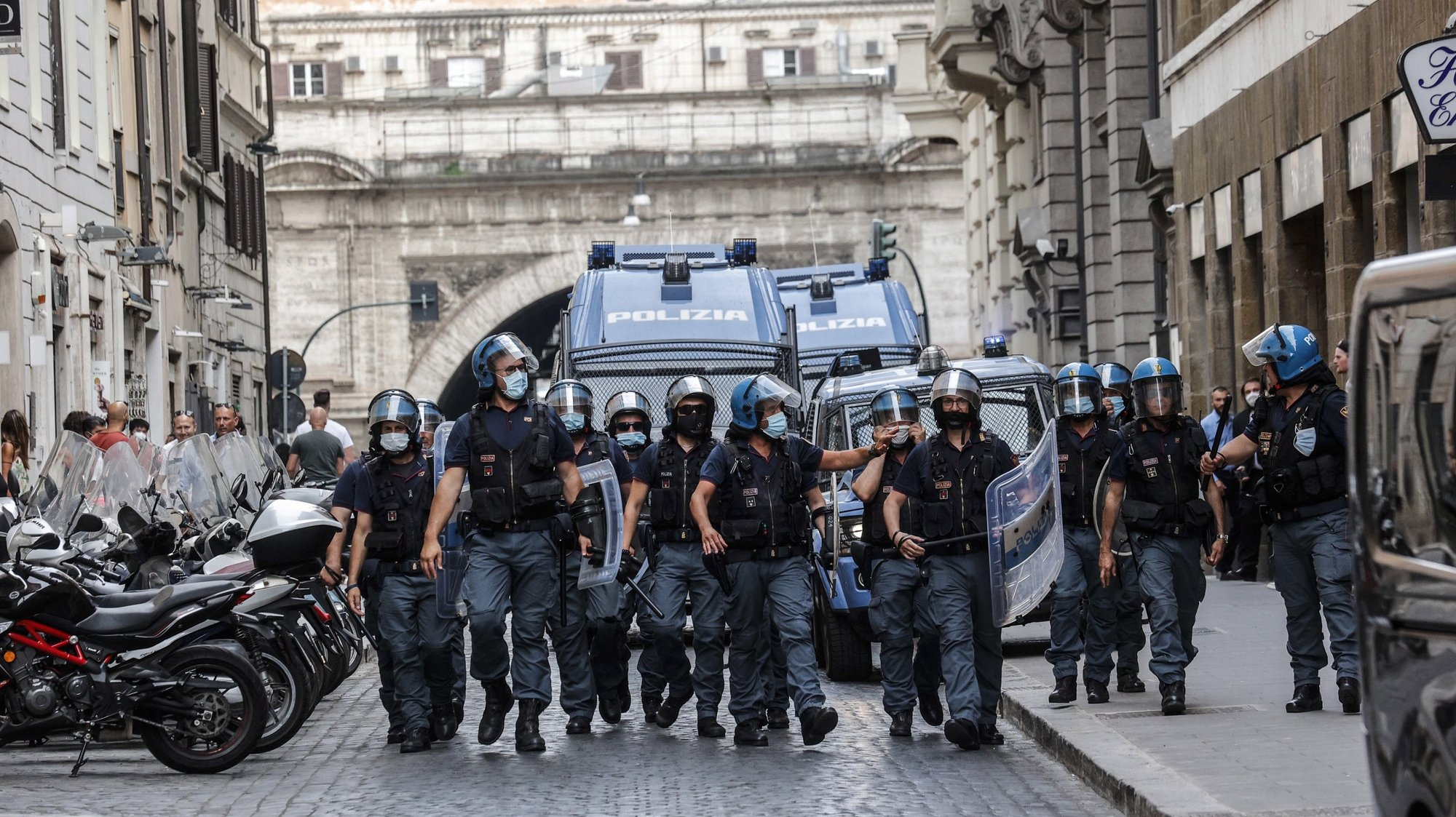 epa09371485 Anti riot police move in during a demonstration against the Green Pass in Rome, Italy, 27 July 2021. The protesters clarified that 'the purpose of the demonstration is not to go against those who want to vaccinate themselves, but give a clear message to the Italian Government that it is not possible to place a mark or a certification to people' and also that 'the Green Pass does not protect, because even those who have made the vaccine can infect, so we don't understand the basic sense, if not that restrictive of personal freedom', the organizers said. According to the Italian government, access to cinemas, stadiums, museums, gyms, swimming pools, theaters, and in-door dining will only be allowed to people carrying the 'Green Pass', a document proving that its carrier received the vaccine against COVID-19, starting 06 August.  EPA/GIUSEPPE LAMI