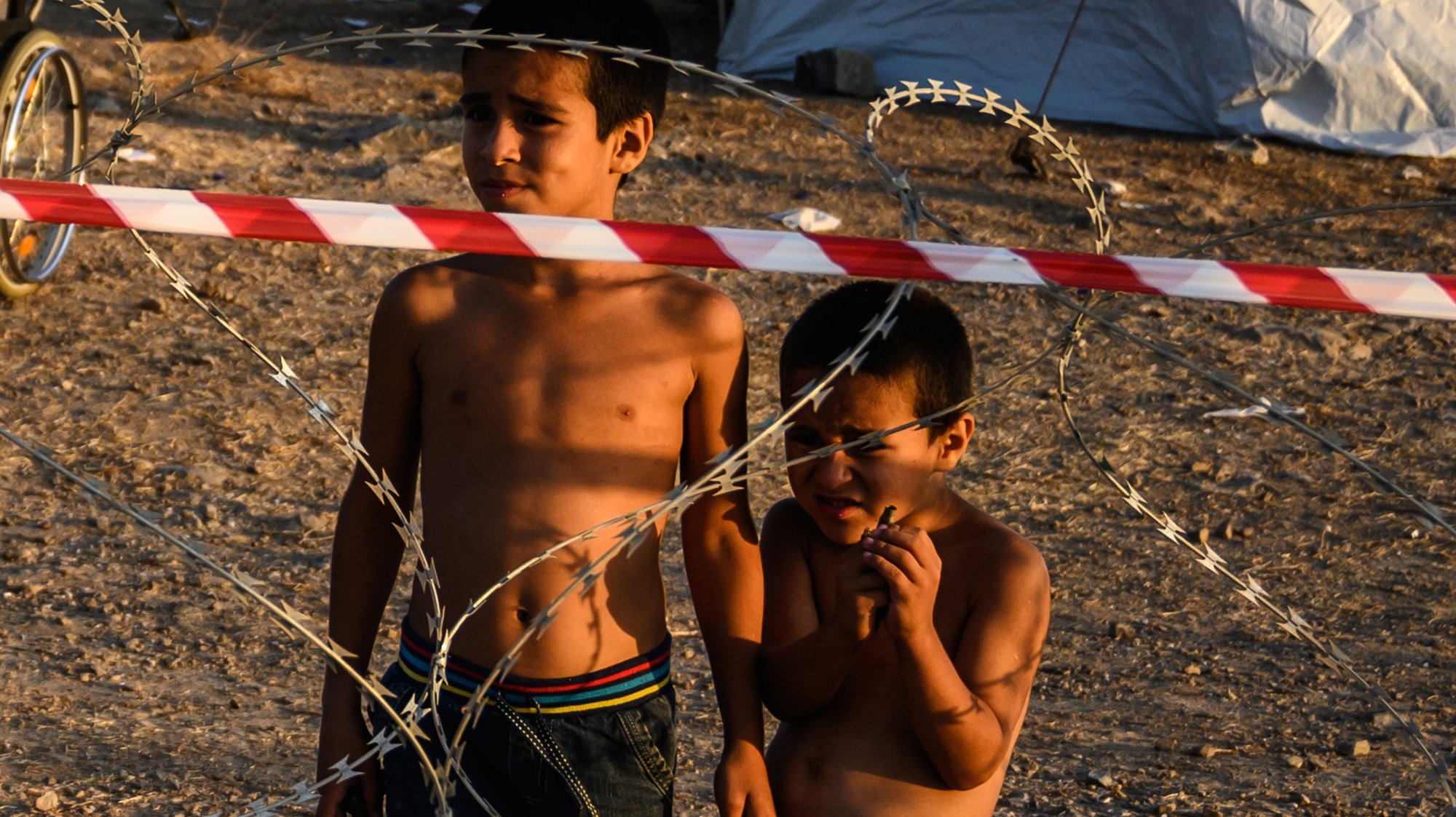 epa08682485 Two small boys stand behind razor wire at Kara Tepe camp on Lesbos island, Greece, 19 September 2020. Following the catastrophic fires at Moria on September 8 and 9, a total of 9,000 people were rehoused at the hotspot of Kara Tepe, south of Mytilini. All of them have been identified and their asylum applications are in process. Of them, 213 were found positive to the novel coronavirus and have been quarantined at separate quarters in the hotspot.  EPA/VANGELIS PAPANTONIS