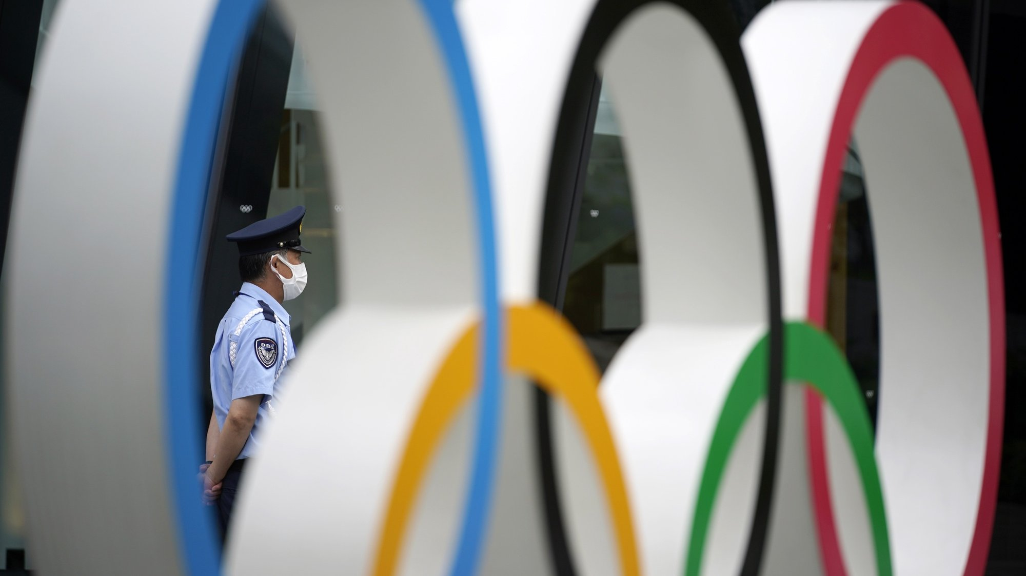 epaselect epa09293117 A security guard is seen through an Olympic Rings monument near the National Stadium, the main stadium of the 2020 Tokyo Olympic Games, in Tokyo, Japan, 22 June 2021. Tokyo will mark one month before the opening of the Tokyo 2020 Olympic Games on 23 June 2021. The Summer Games were postponed due to COVID-19 Coronavirus pandemic.  EPA/FRANCK ROBICHON