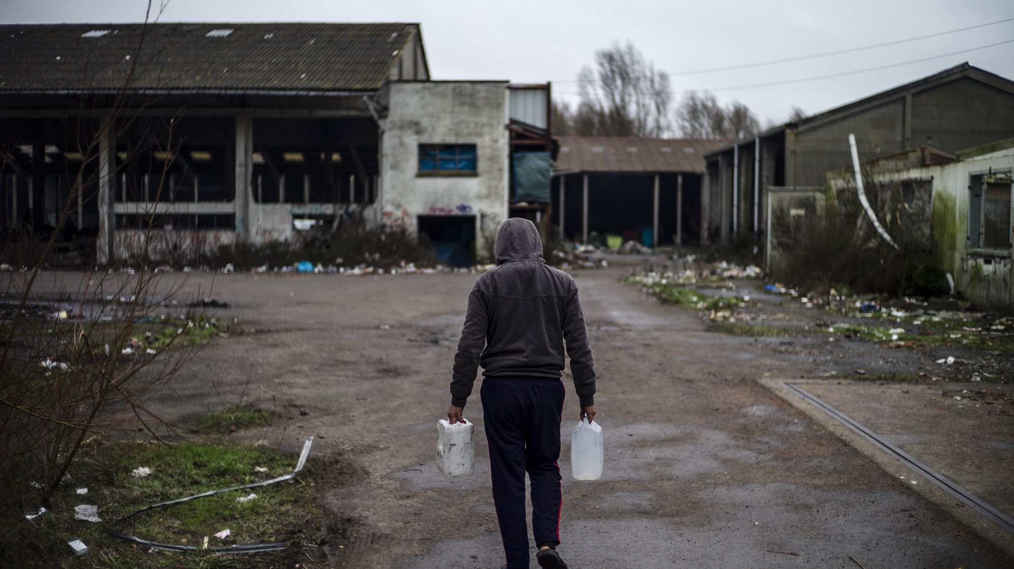 epa08179161 A refugee carries water inside the makeshift migrant camp in Grande-Synthe, near Dunkerque, France, 30 January 2020. The camp in Grande-Synthe counts an estimated 500 residents mostly composed of Kurds from Iraq. They are still hoping to reach United Kingdom even if Britain is due to leave the European Union on 31 January 2020.  EPA/YOAN VALAT