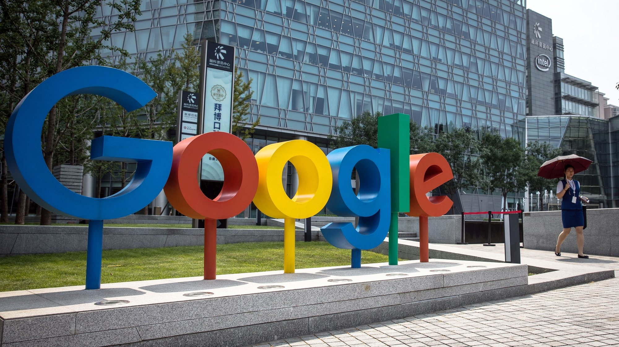 epa08979756 (FILE) - A Chinese woman walks past a 'Google' brand name and logo, near the Google office in Beijing, China, 03 August 2018 (reissued 01 January 2021). Alphabet, the parent company of internet giant Google, is due to publish their 4th quarter 2020 results on 02 January 2021.  EPA/ROMAN PILIPEY *** Local Caption *** 54599547