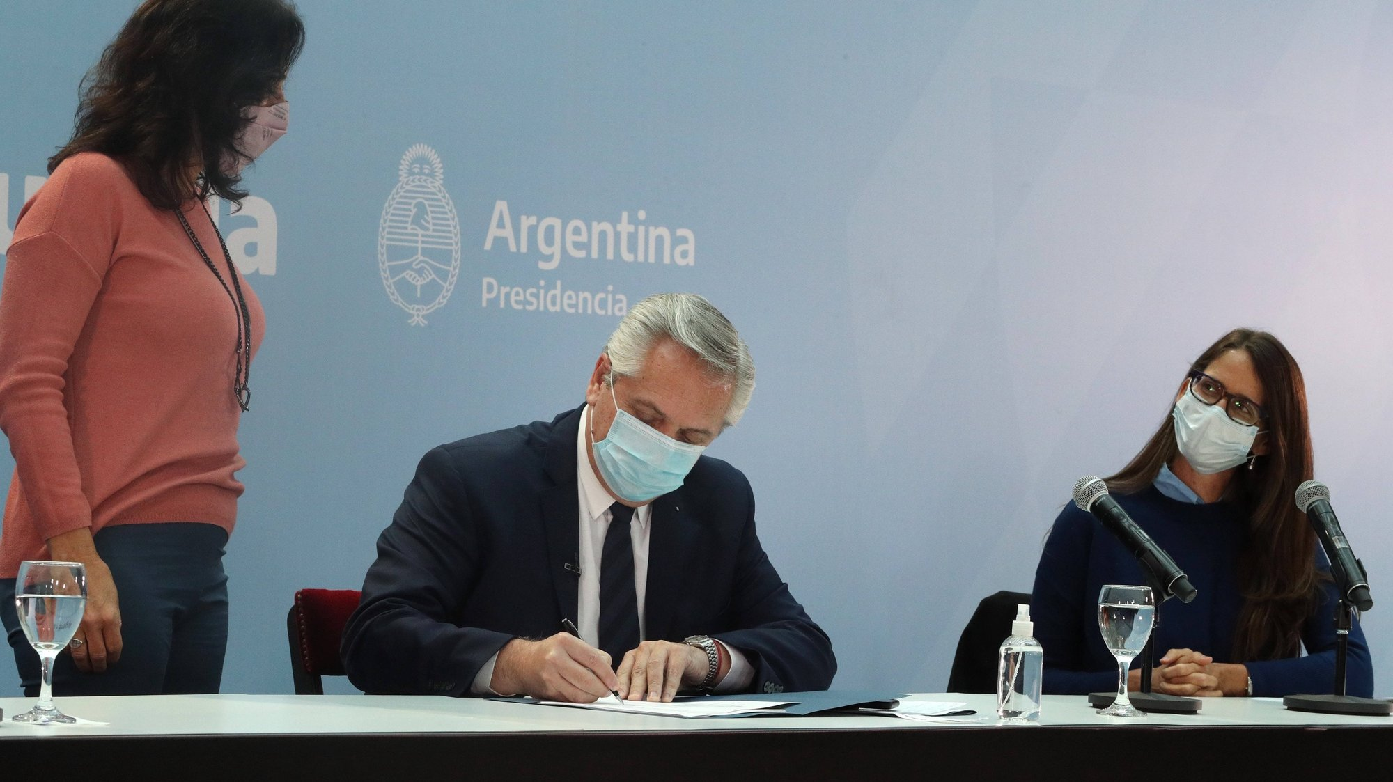 epa09329420 A handout photo made available by the Argentinian Presidency that shows President Alberto Fernandez (C) while signing the law that protects the labor quota of transgender public workers, in Buenos Aires, Argentina, 07 July 2021. The Government of Argentina promulgated this 07 July the law that establishes a labor quota for transvestites, transsexuals and transgender people in the public sector, approved at the end of last June, in an act that was attended by President Alberto Fernandez.  EPA/Argentinian Presidency / HANDOUT THIS IMAGE IS TO BE USED SOLELY TO ILLUSTRATE NEWS REPORTING OR COMMENTARY ON THE FACTS OR EVENTS DEPICTED IN THIS IMAGE WITH THE ORIGINAL TEXT (MANDATORY CREDIT) HANDOUT EDITORIAL USE ONLY/NO SALES