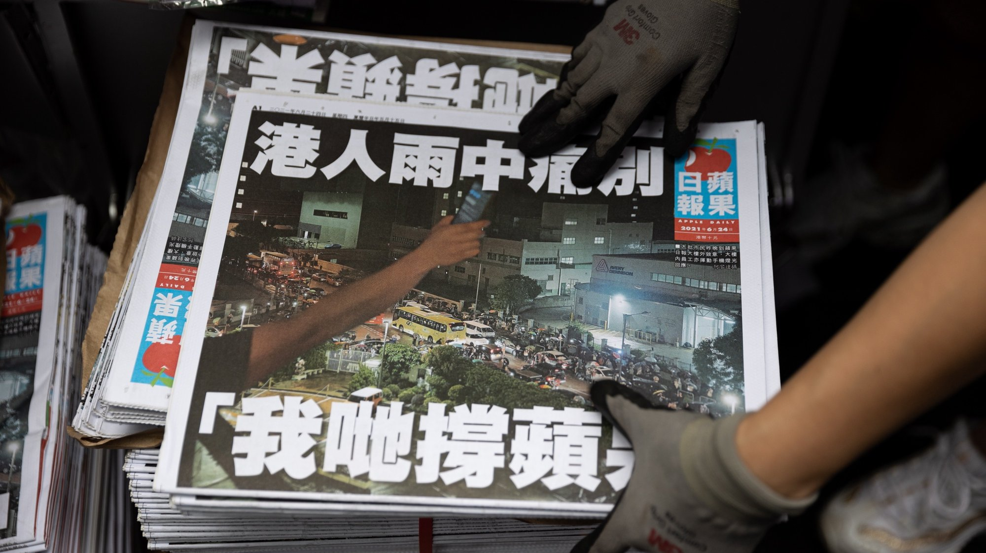 epa09297881 A salesperson stocks Apple Daily's final issue at a news stand in Central, Hong Kong, China, 24 June 2021. The last edition of Apple Daily rolled off the presses three days earlier than expected, after management took into consideration the safety of its staff and manpower concerns.  EPA/JEROME FAVRE