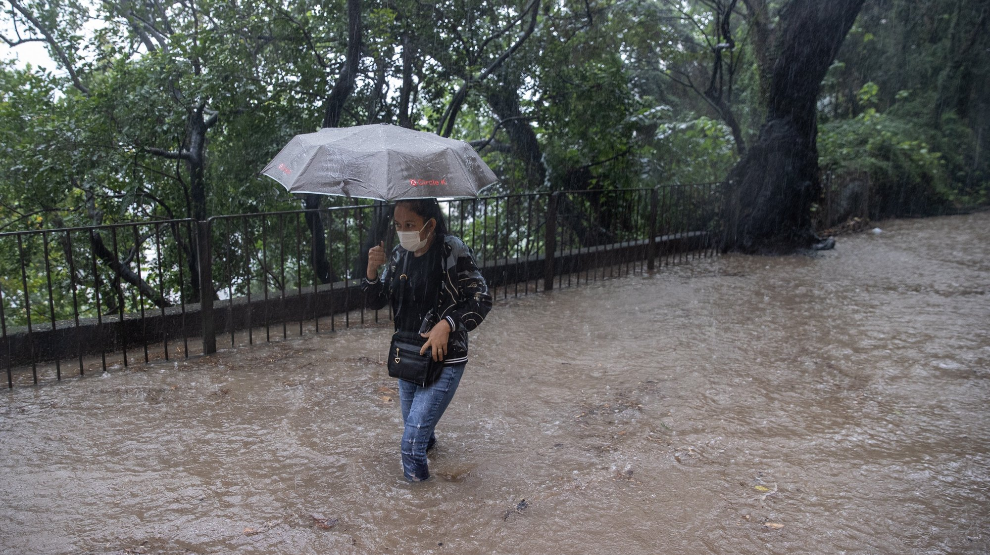 epa09512550 A woman makes her way in a road flooded by rain brought by tropical storm Lionrock in Hong Kong, China, 08 October 2021. The Hong Kong Observatory briefly upgraded its rainstorm warning to black, the highest level, amid torrential downpours brought by tropical storm Lionrock this morning.  EPA/JEROME FAVRE