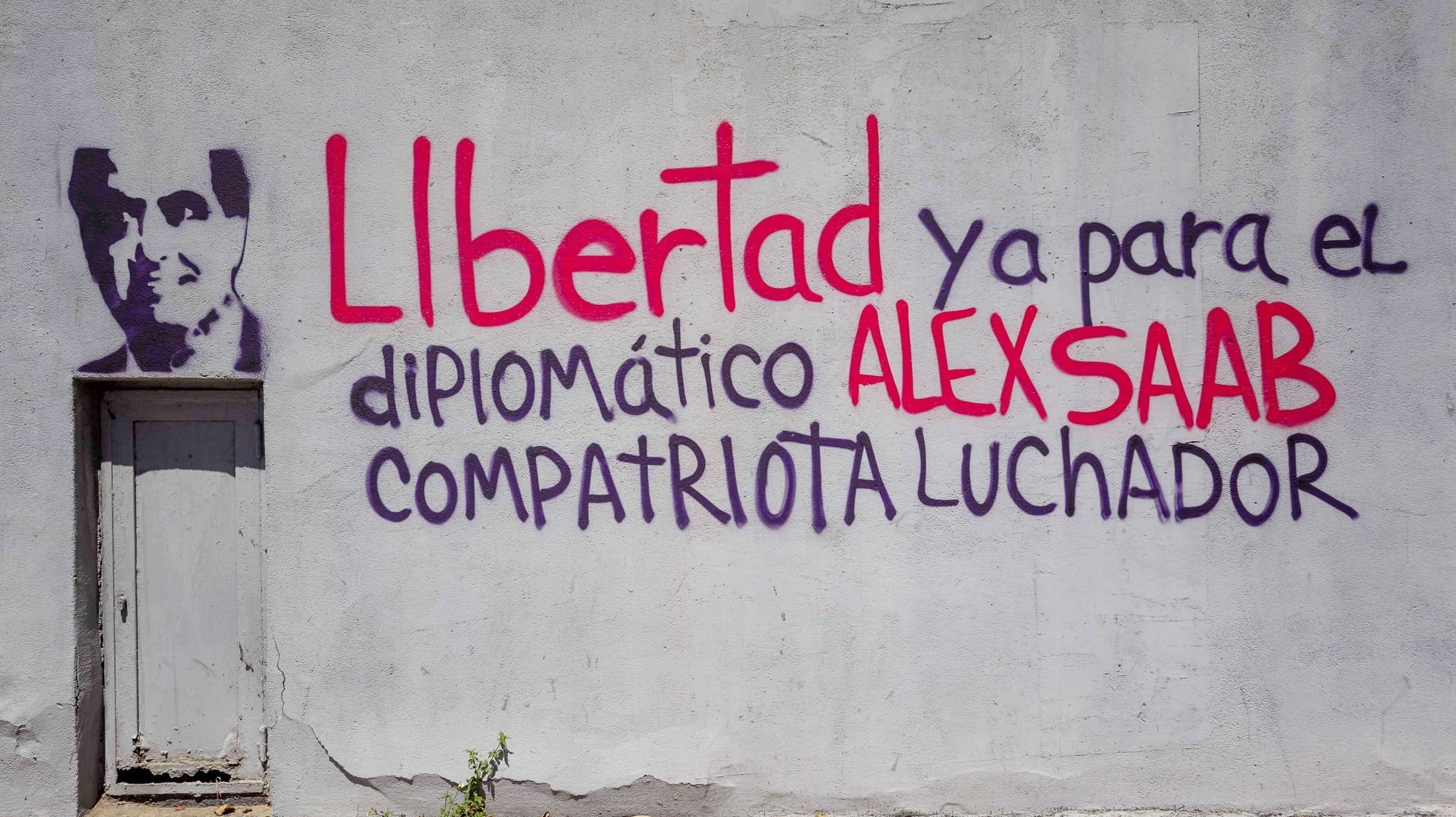 epa09024179 A graffiti oim support of Alex Saab reading 'Freedom now for the diplomat Alex Saan compatriot fighter' at wall of the ruling party PDVSA headquarters in Caracas, Venezuela, 19 February 2021. Venezuelan diplomat Alex Saab was arrested in Cape Verde in June 2020 at the request of the USA for alleged financial crimes, he was later placed under house arrest in January 2021.  EPA/Miguel Gutiérrez