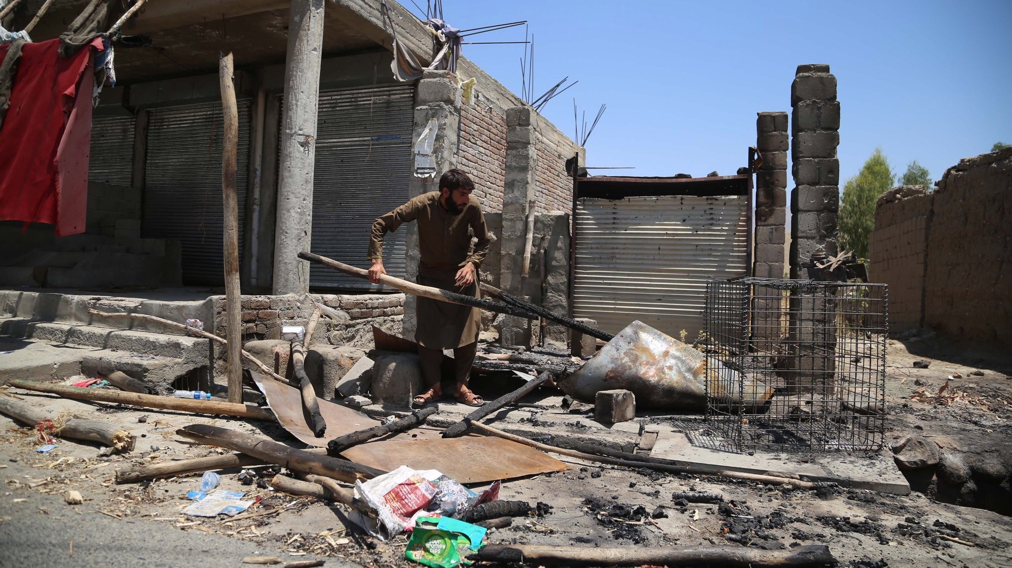epa09330986 An Afghan man salvages his belongings from his shop that was burnt out during an operation against Taliban militants after security forces cleared the area of Taliban militants following an operation in Alishang district of Laghman province, Afghanistan, 08 July 2021. The Afghan government 06 July, confirmed that the insurgents had captured more than 100 of the country's 400 districts, which it blamed on a lack of military support to the Afghan forces after the pullout of international troops. The United States and NATO troops began the final stages of withdrawal more than two months ago, ending a 20-year mission and handing over nearly all military bases to the Afghan army.  EPA/GHULAMULLAH HABIBI