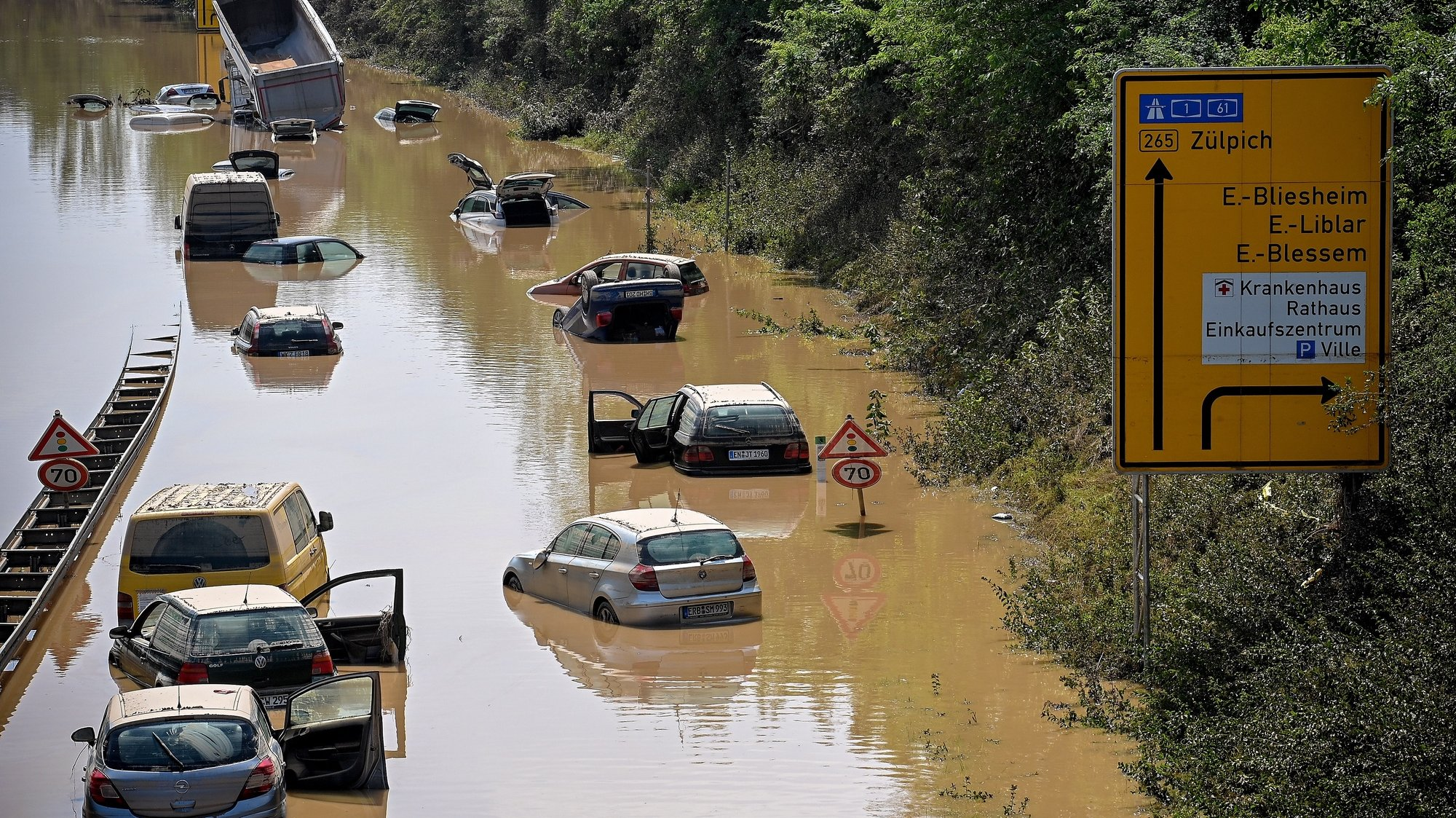 epaselect epa09351311 Wrecked cars and trucks are flooded on the B265 federal highway in Erftstadt, Germany, 17 July 2021. Large parts of Western Germany were hit by heavy, continuous rain in the night to Wednesday, resulting in local flash floods that destroyed buildings and swept away cars.  EPA/SASCHA STEINBACH