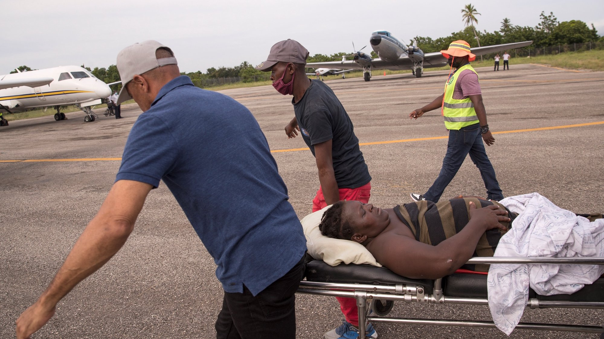 epa09420689 Some men carry a woman injured during the earthquake on a stretcher to be transferred by plane to a hospital in Port-au-Prince, from Les Cayes, Haiti, 19 August 2021. At least 2,189 people died and 12,268 were injured as a result of the 7.2 earthquake that devastated much of southern Haiti on August 14, in addition to substantial material losses, according to the latest official count.  EPA/ORLANDO BARRIA
