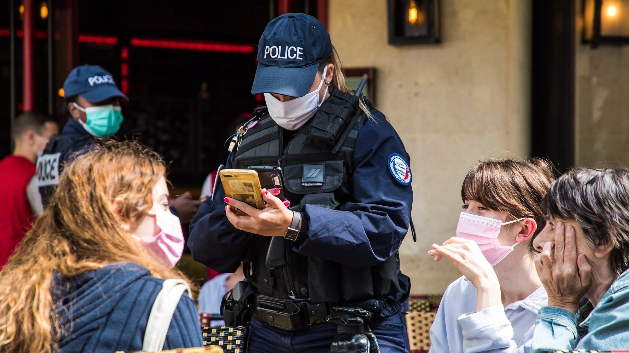 epa09407160 French police officers control customers' health passes at a bar in Paris, France, 09 August 2021. Starting from 09 August, the Covid-19 pass will be required in France to access cafes, restaurants, long-distance travel and, in some cases, hospitals. It was already in place for cultural and recreational venues, including cinemas, concert halls, sports arenas and theme parks with a capacity for more than 50 people.  EPA/CHRISTOPHE PETIT TESSON