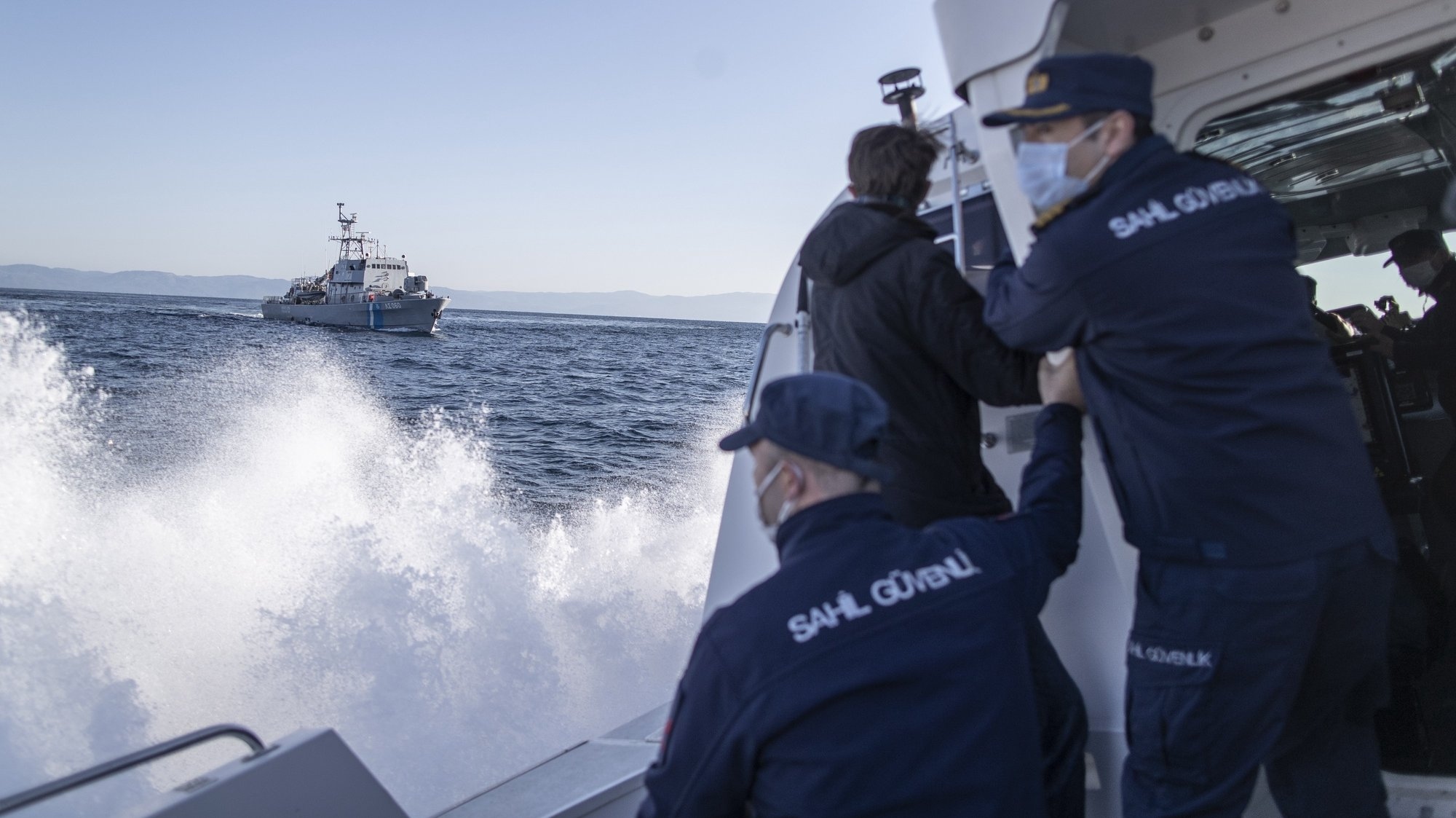 epa09131071 Members of the Turkish Coast Guard give a warning to a Greece Coast Guard ship, which allegedly crossed into Turkish waters, during a patrol to search and rescue for migrants as they pass to or pushed back from Lesvos Island of Greece offshore the Ayvalik district in Balikesir, Turkey, 10 April 2021 (issued 12 April 2012). The Greek island of Lesbos hosts one of the hotspots, an initial reception centers for migrants in European Union. Turkish authorities told epa/Efe that in 2020 around 45 percent of migrants rescued in the Aegean Sea had been pushed back from Greek territory. Most common cases involve migrant vessels being stopped by a Greek patrol when entering Greek waters, but the Turkish coastguard says it has heard lots of migrants describing 'delayed pushback,' when people are returned to the sea days after they reached Lesbos. According to Turkish officials, in this case, a Greek patrol carries the detained migrants to the limit of Greek territorial waters before putting them in a life raft and alerting Ankara.  Since the beginning of 2021, Turkey has rescued around 2,700 migrants in the Aegean Sea, and some 1,900 migrants from a pushback.  The Norwegian NGO Aegean Boat Report claims, some 558 people have been abandoned on 35 life rafts at sea so far in 2021. Some such incidents have ended with fatalities, the organizations claimed.  EPA/ERDEM SAHIN  ATTENTION: This Image is part of a PHOTO SET