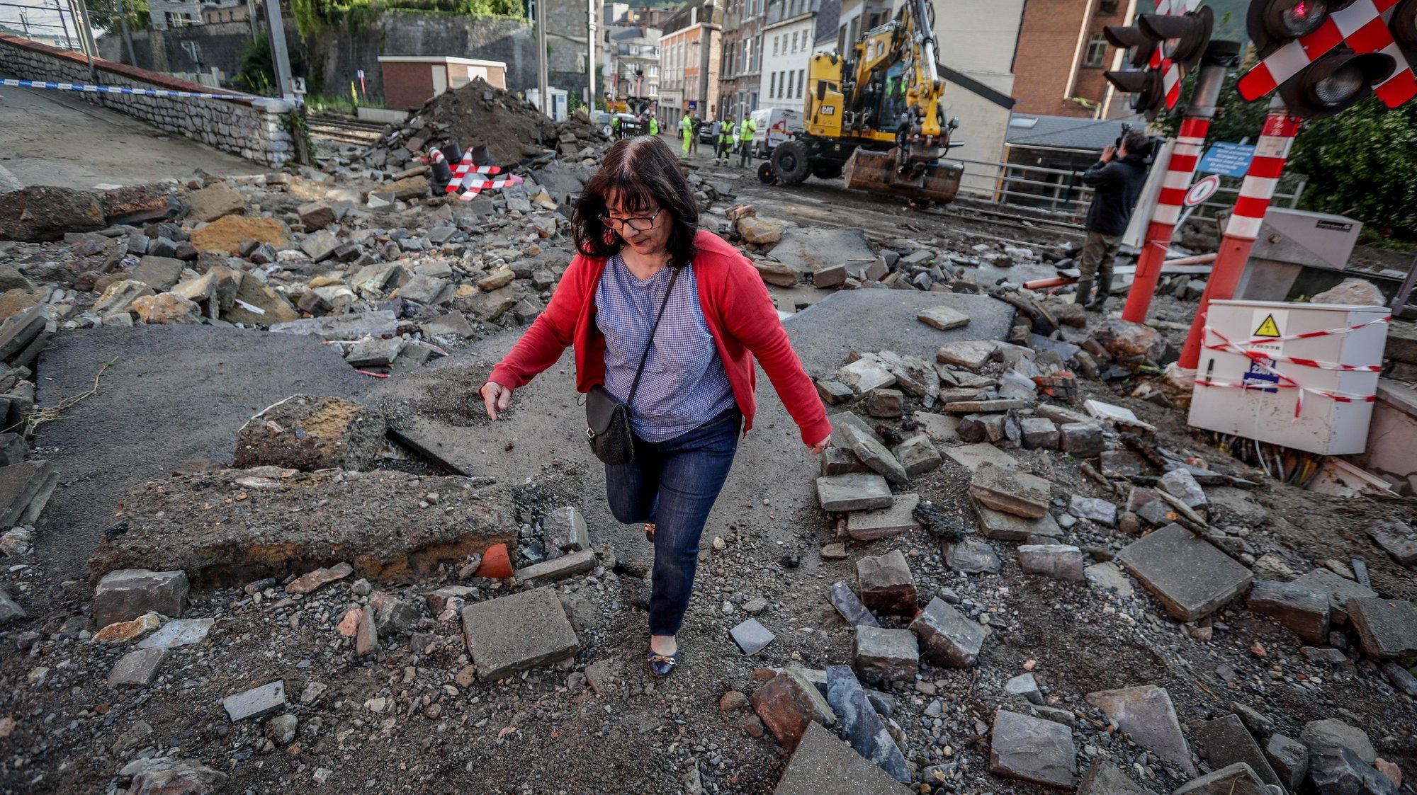 epa09364158 A woman walks in the rubble after flooding due to heavy rains on 24 July, in Dinant, Belgium, 25 July 2021. Heavy rains caused widespread damage and flooding in parts of Belgium and across central Europe in the night of 14/15 July. Dozens have died and many remain unaccounted for. On July 24, more rain fell over southern Belgium.  EPA/STEPHANIE LECOCQ