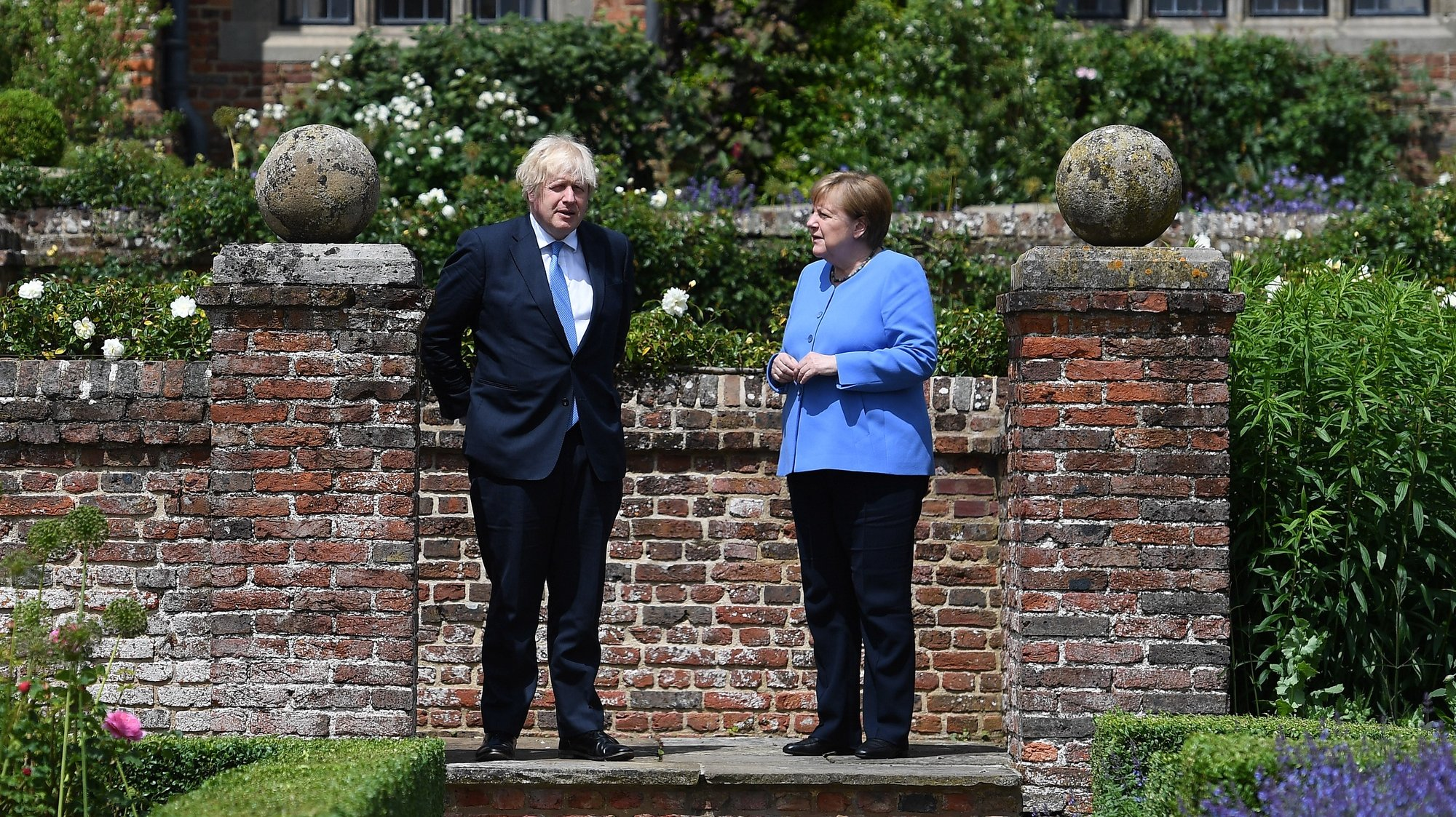 epa09317444 British Prime Minister Boris Johnson (L) with German Chancellor Angela Merkel (R) in the rose garden at the Prime Minister's country residence at Chequers, Buckinghamshire, Britain, 02 July 2021. The two nations have agreed a post Brexit  joint declaration on foreign and security policy cooperation. The bilateral agreement is the first to be struck between London and Berlin on foreign and security policy issues.  EPA/ANDY RAIN / POOL Pool