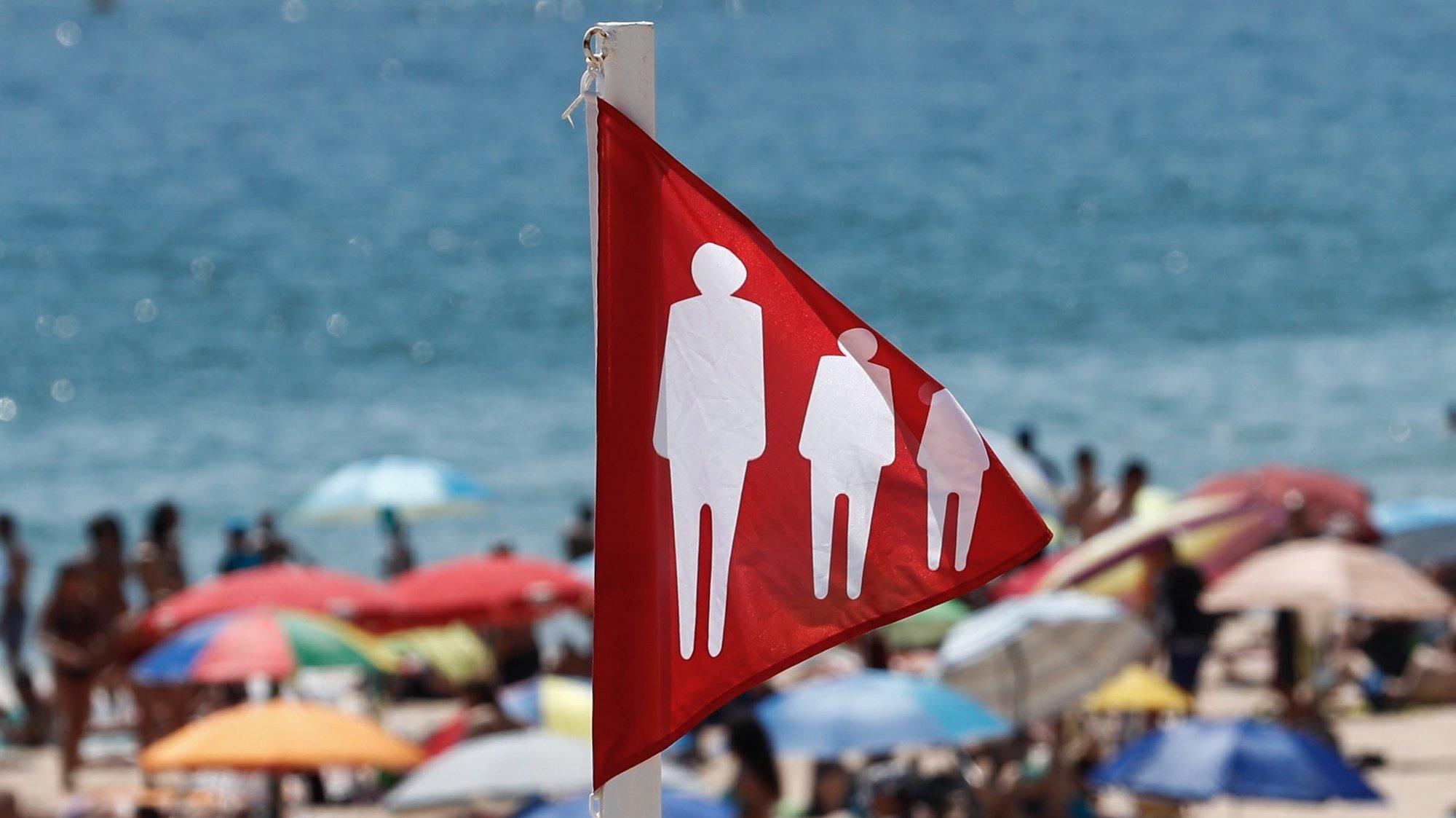 Mesmo com a bandeira vermelha hasteada correspondente à ocupação plena da praia devido à pandemia provocada pela covid-19, as pessoas aproveitam as altas temperaturas que se fazem sentir, na praia de Carcavelos, Cascais, 05 de julho de 2020. ANTÓNIO COTRIM/LUSA
