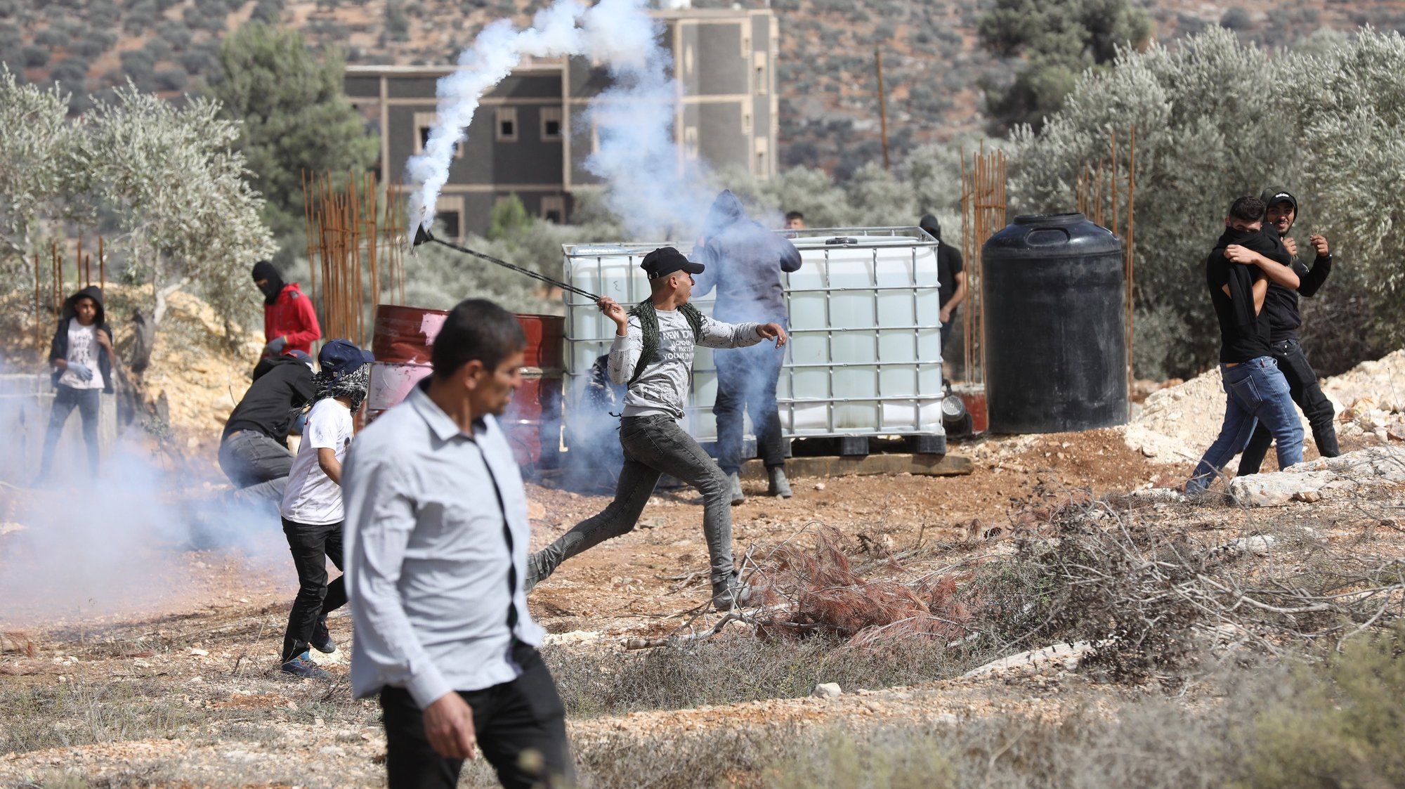 epa09485731 A Palestinian protestor throws back a tear gas grenade during clashes with Israeli security forces after a protest against Israeli settlements, on the lands of Beita village near the West Bank city of Nablus, 24 September 2021.  EPA/ALAA BADARNEH