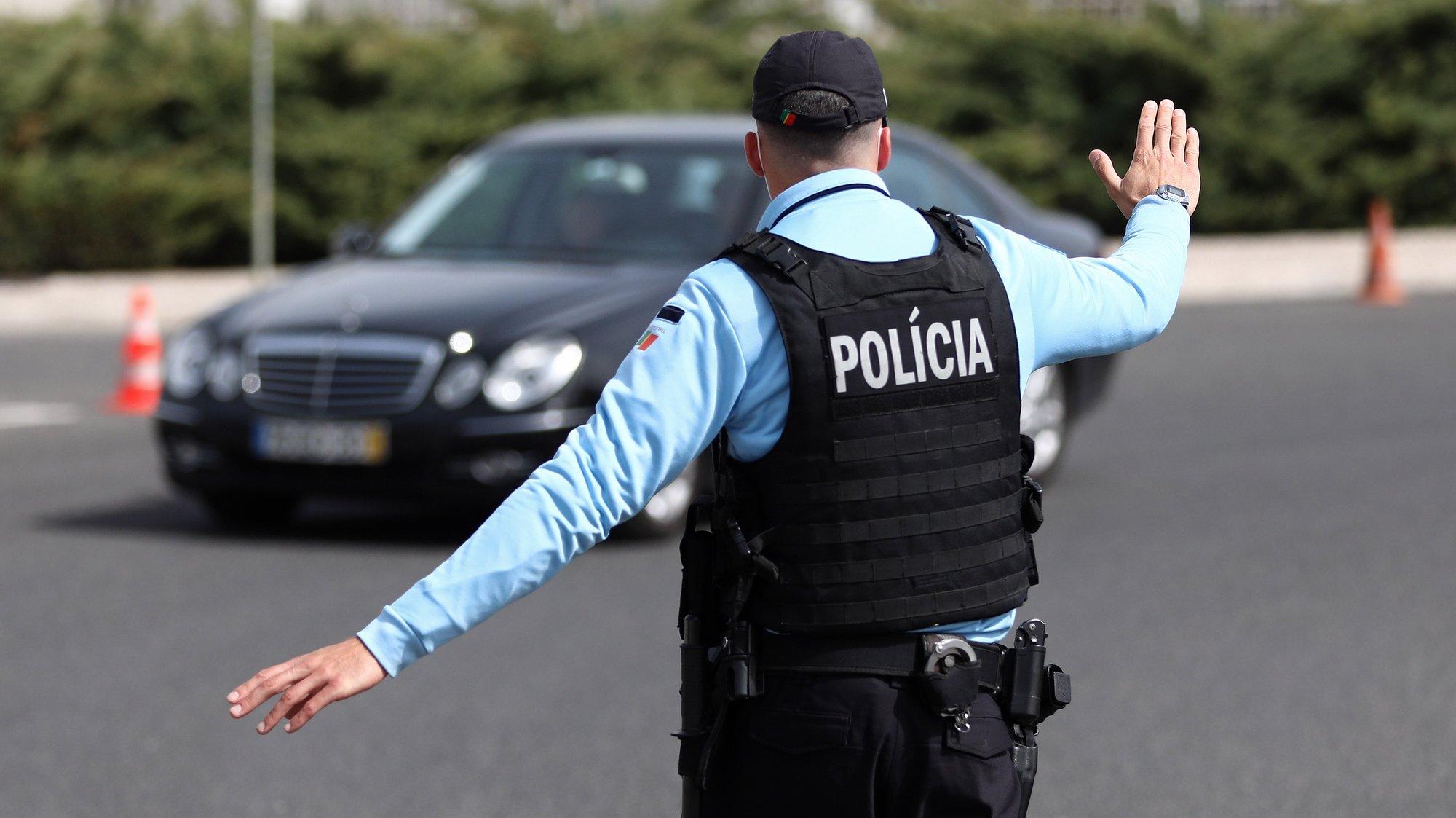 Um agente da PSP controla automobilistas e passageiros durante o confinamento que se prolonga até ao dia 05 de abril, no âmbito das medidas de contenção da pandemia de covid-19, em Oeiras, 27 de Março de 2021. A circulação entre concelhos em Portugal continental está proibida desde as 00:00 de ontem e as 05:00 de 05 de abril, no âmbito do estado de emergência para combater a pandemia de covid-19. ANTÓNIO PEDRO SANTOS/LUSA