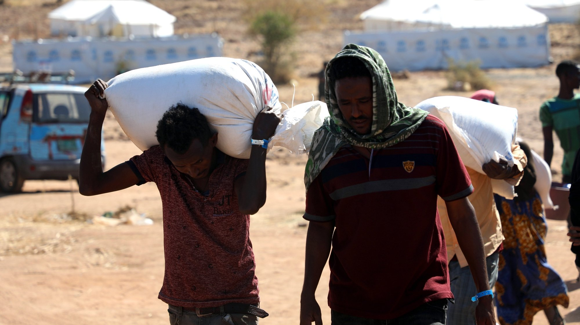 epa08849883 Refugees carrying flour at Um Rakuba refugee camp in the state of al-Qadarif (also known as Gedaref), Sudan, 28 November 2020. The number of refugees in this camp reached nearly 10,000 refugees who crossed the border from Ethiopia to Sudan to escape the conflict in Tigray region of Ethiopia.  EPA/MOHAMMED ABU OBAID