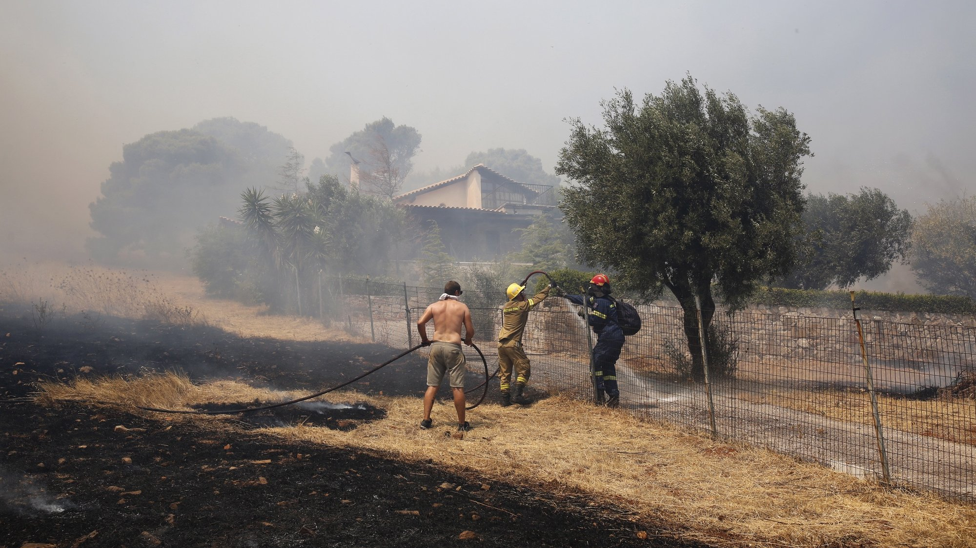 epa09416330 Firefghters and volunteers battle blazes raging near a house during a wildfire that broke out in the area of Keratea, some 40 km away from Athens city, Greece, 16 August 2021. Three settlements in the area of Keratea have been evacuated and the traffic in the area has been interrupted. Meanwhile, another wildfire broke out at a forest area in Villia, Attica region.  EPA/ALEXANDROS VLACHOS