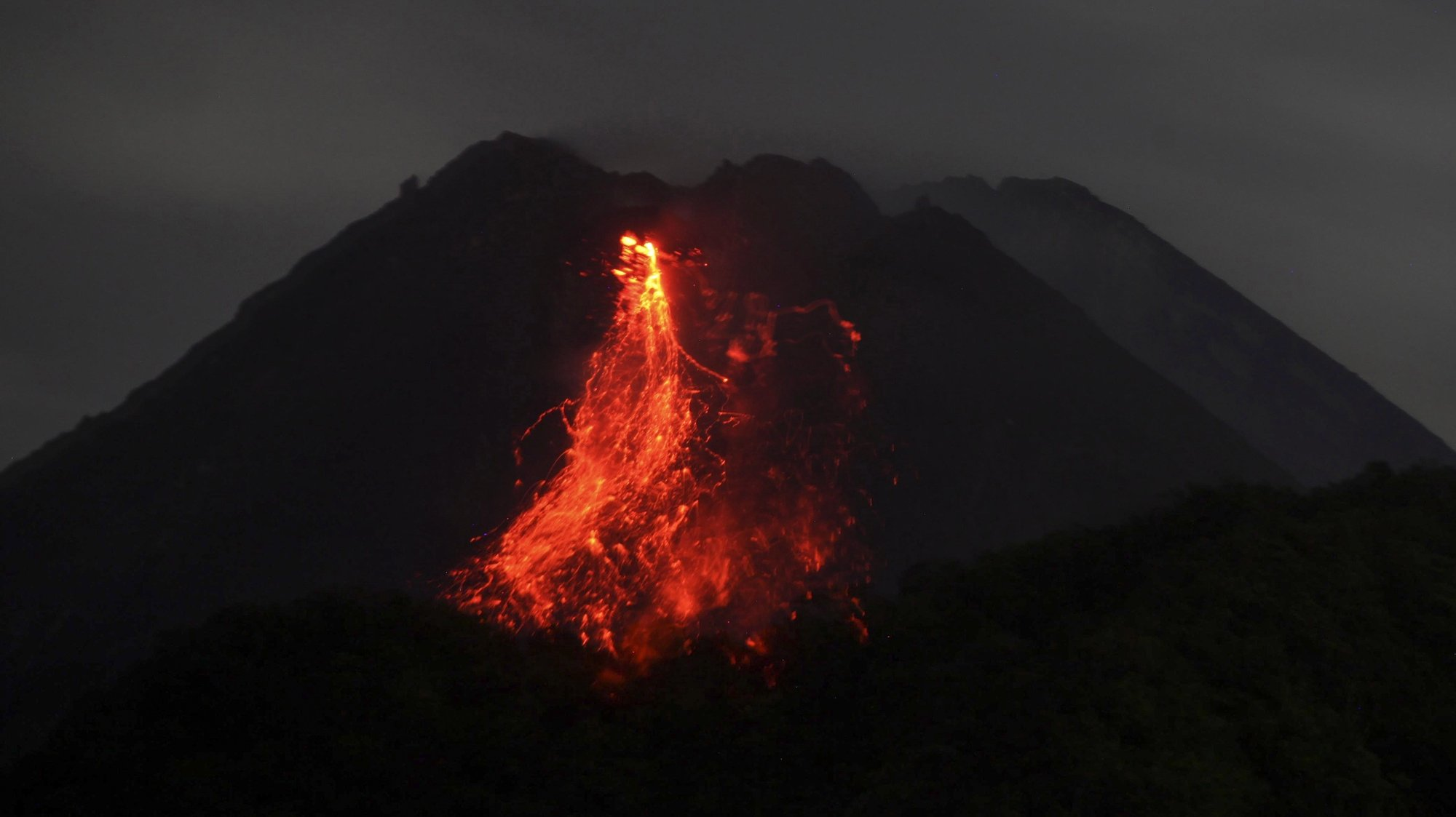 epaselect epa08945381 Mount Merapi volcano spews lava during an eruption, as seen from Sleman, Yogyakarta, Indonesia, 17 January 2021 (issued 18 January 2021). Mount Merapi is one of the most active volcanoes in the country. At least 300 people were killed when it erupted in 2010.  EPA/BOY TRIHARJANTO
