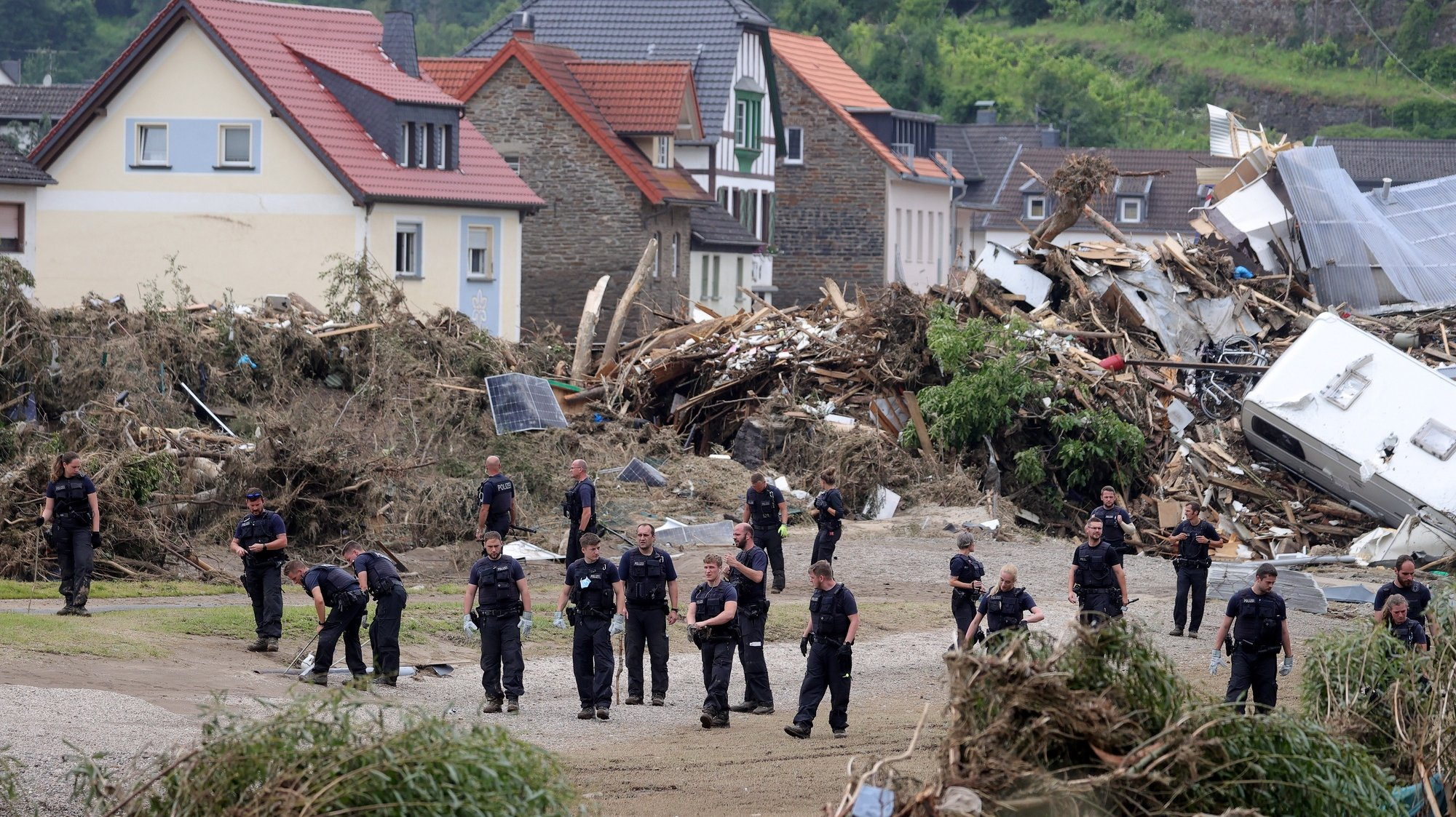 epa09353802 Police officers inspect the area after the flooding of the Ahr River, in Altenahr, Germany, 19 July 2021. Large parts of western Germany and central Europe were hit by flash floods in the night of 14 to 15 July, following days of continuous rain that destroyed buildings and swept away cars. The total number of victims in the flood disaster in western Germany rises to at least 164, with many hundreds still missing.  EPA/FRIEDEMANN VOGEL