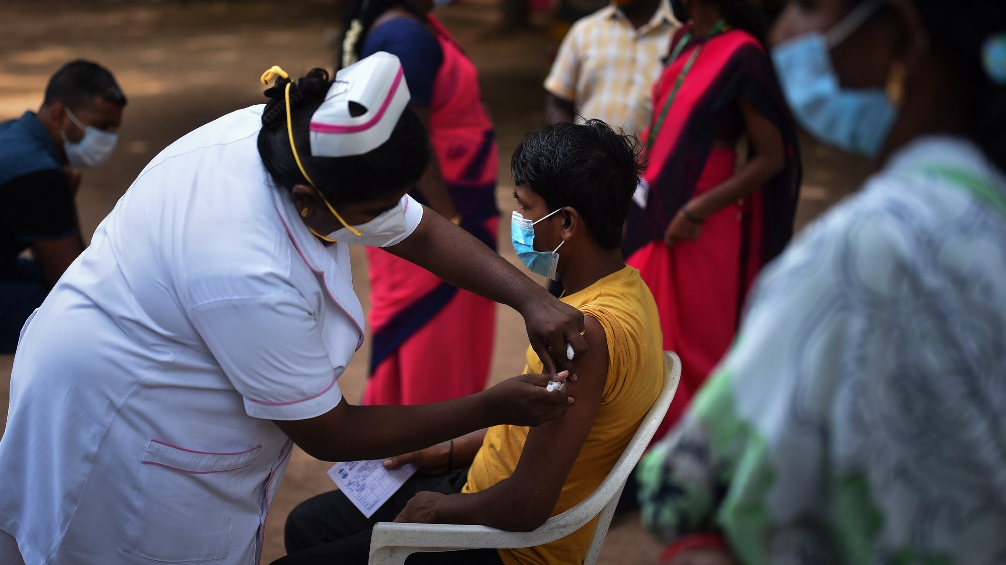epa09463272 An Indian health worker administers a dose of COVID-19 vaccine to a man during a state wide mega-vaccination drive against the COVID-19 coronavirus, at a government school in Chennai, India, 12 September 2021. The Tamil Nadu state government organized a mega COVID-19 vaccination drive across the state for 12 hours from 7 am to 7 pm, which aims to inoculate around 2 million people above 18 years  in 40,000 government centers on 12 September 2021. The state government is conducting the mega vaccination drive to avoid the possible third COVID-19 wave. The Greater Chennai Corporation (GCC) has set-up 1600 special vaccination camps as part of the state wide mega COVID-19 vaccination drive in Chennai.  EPA/IDREES MOHAMMED