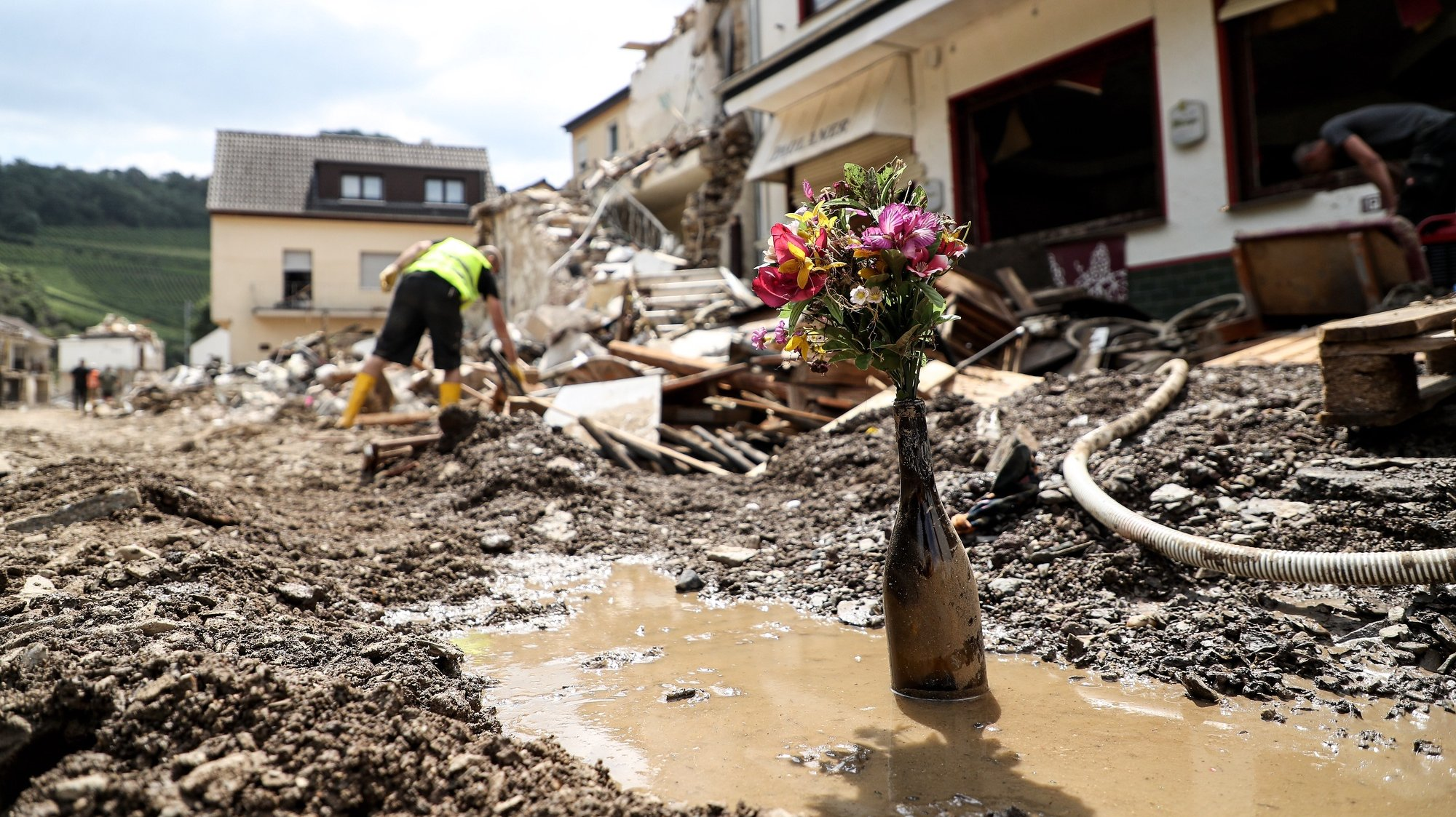 epaselect epa09358245 Flowers in a wine bottle standing in front of a destroyed house after the flooding of the Ahr River, in Mayschoss in the district of Ahrweiler, Germany, 22 July 2021. Large parts of Western Germany were hit by heavy, continuous rain in the night to 15 July resulting in local flash floods that destroyed buildings and swept away cars.  EPA/FRIEDEMANN VOGEL